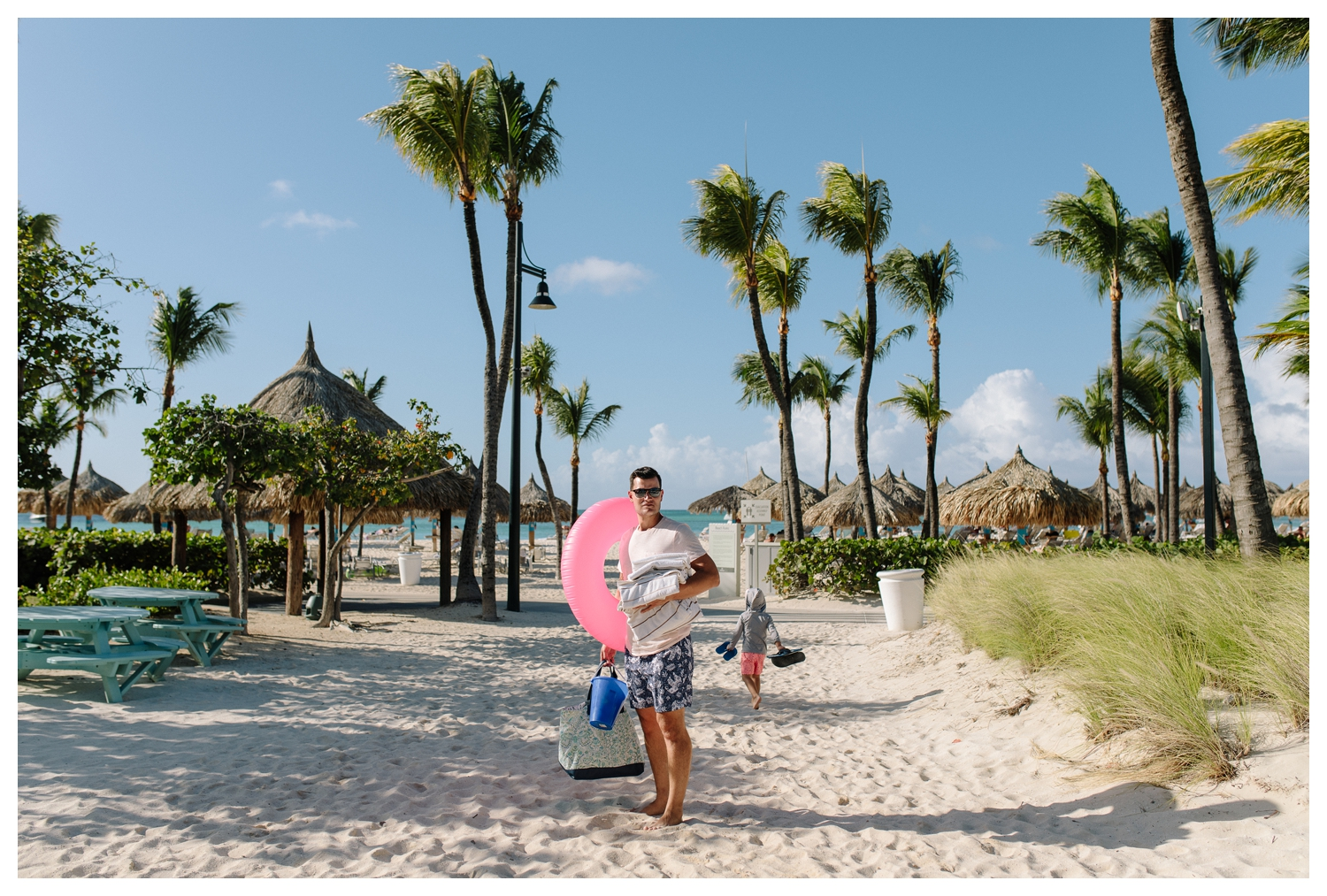 Dad Carrying Pink Float on Aruba's Beach Family Vacation.jpg