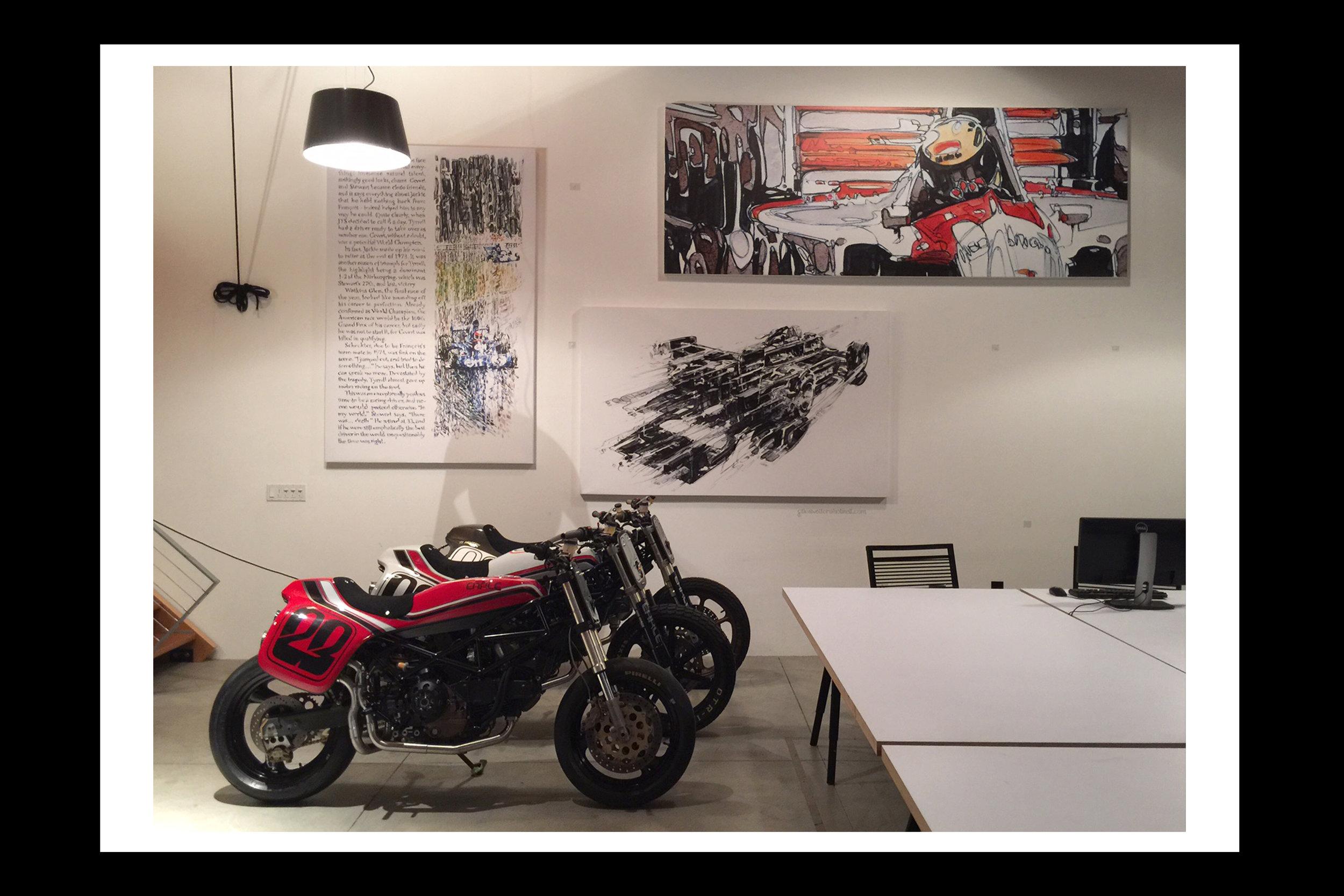 3 prints hanging behind 3 of Earl Motors bespoke Ducati's.