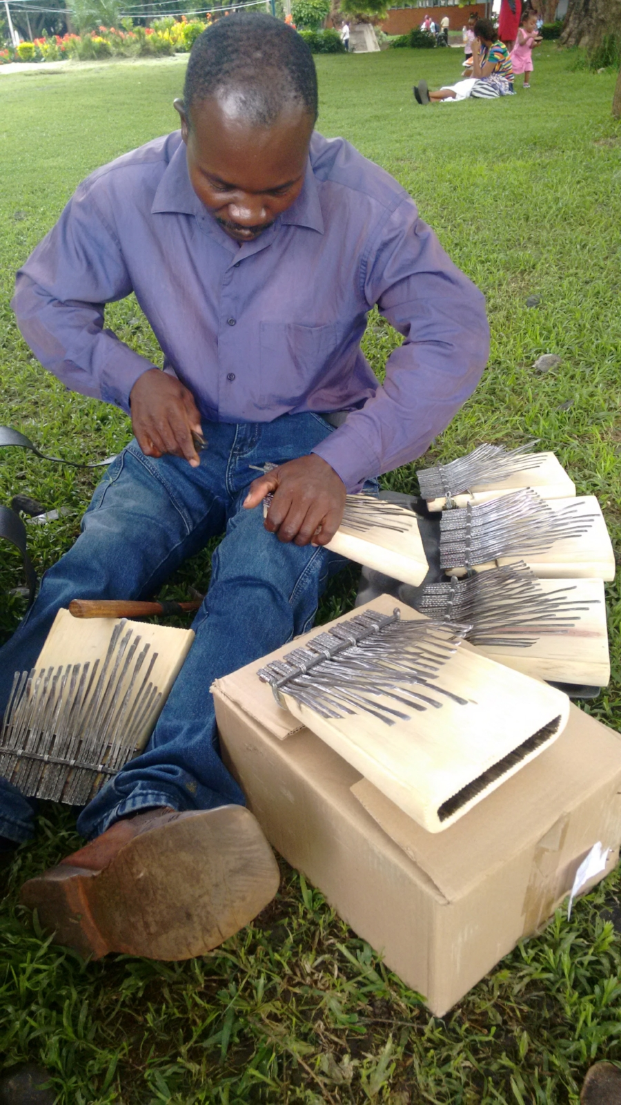 James Kamwaza tuning hera mbira in the park before shipping them.