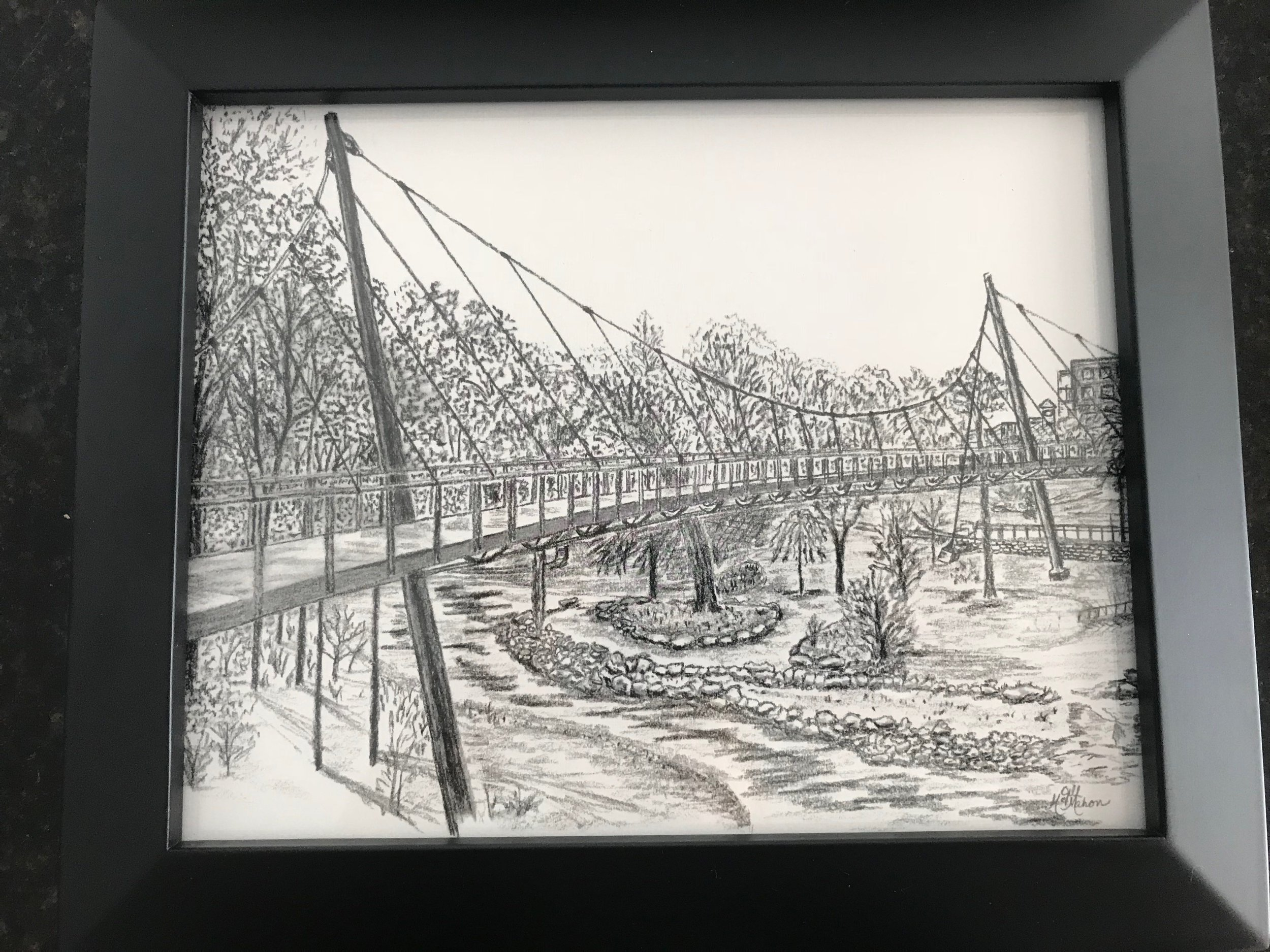 LIBERTY BRIDGE CHARCOAL PRINT   Decorate your home with this framed 8x10 print of a charcoal drawing of the iconic Greenville landmark - Liberty Bridge.  DONOR: Jill McMahon VALUE: $60