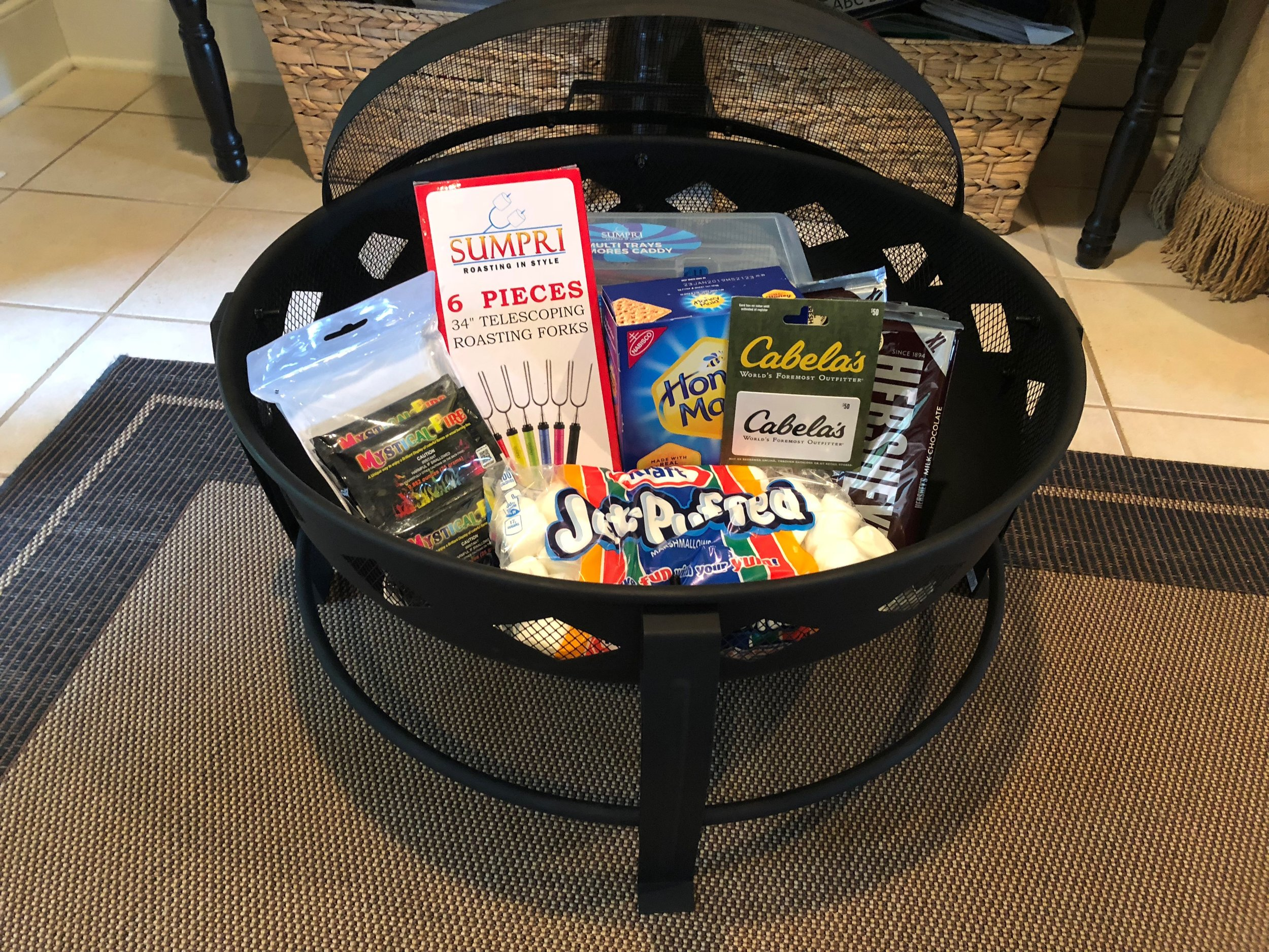 CAMPFIRE BASKET   Roast s'mores in style with this Landmann Firepit full of goodies! Included are $50 Cabela's gift card, S'mores Caddy, S'mores ingredients--Hershey bars, bag of marshmallows, box of graham crackers, 6 piece roasting forks and 12-pack Mystical Fire.  DONOR: 2nd Grade Classes VALUE: $160