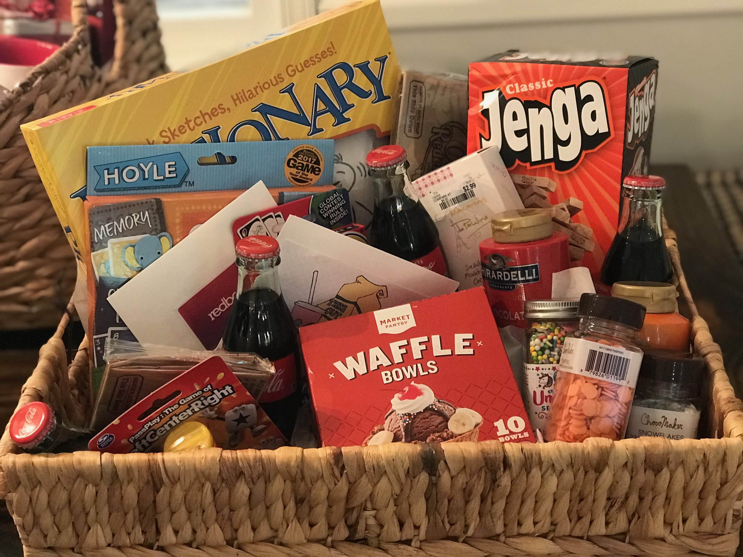 TAKEOUT, ICE CREAM, GAMES AND MOVIE NIGHT BASKET   Stay in with the family and order out for a fun night of games and a movie. Included are $25 for takeout, Redbox gift card, Pictionary, Jenga, 6-in-1 Cards, Left Right Center, Uno and a deck of cards, fixin's for ice cream sundaes, popcorn and snacks.  DONOR: 1st Grade Classes VALUE: $125