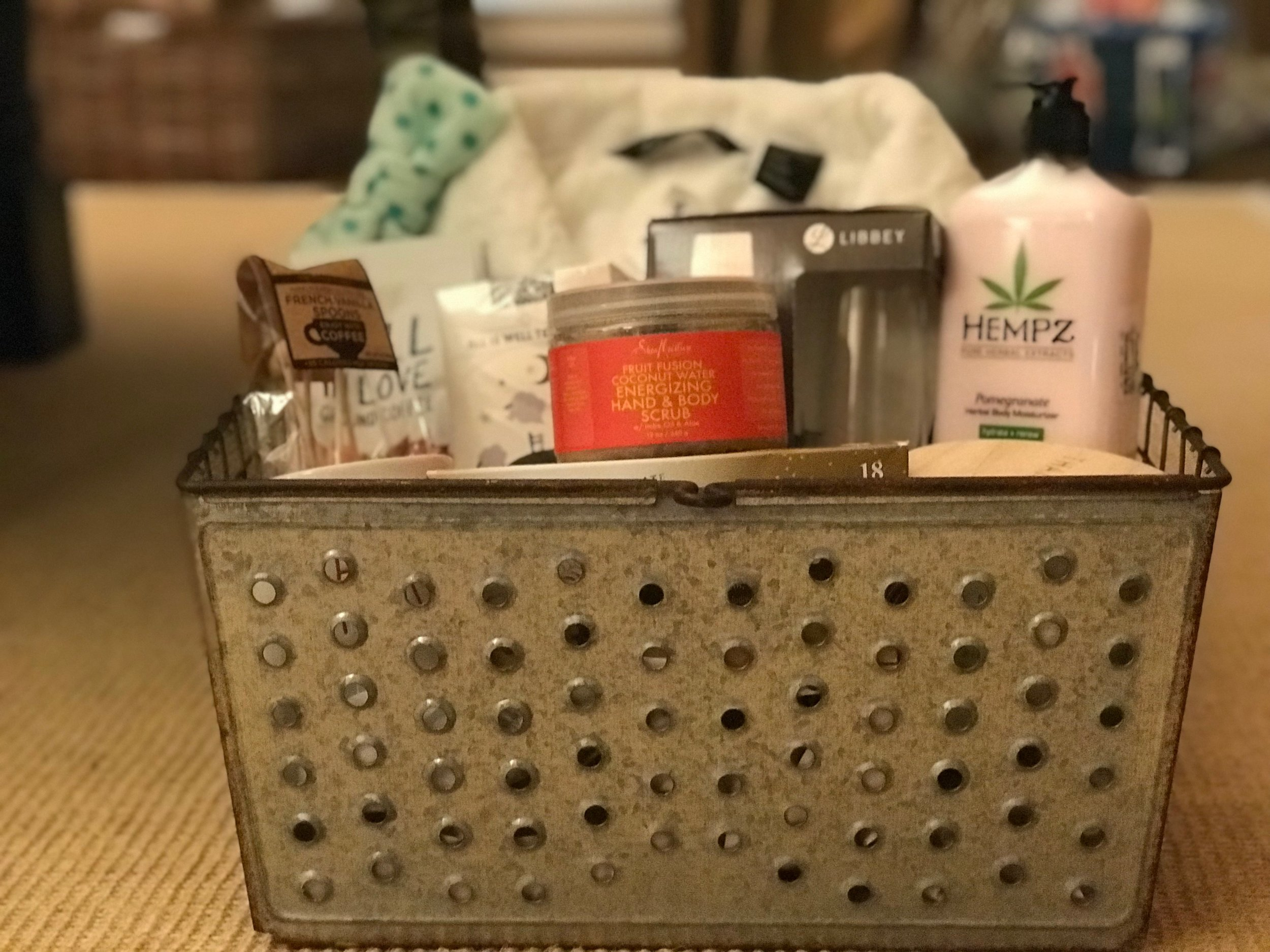 AT HOME SPA DAY BASKET   Pamper yourself in the comfort of your own home with this luxurious basket of goodies. Included are a cozy robe, make up/face wash headband, body scrub and lotion, coffee with mug and spoons, herbal tea, sparkling grape juice with stemless flute glasses, and Belgian chocolate pralines in a cute metal storage basket.  DONOR: 3rd Grade Classes VALUE: $95