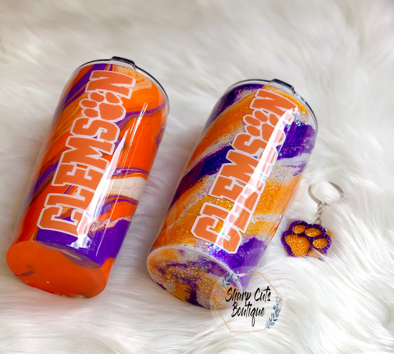 CUSTOM HYDRO DIPPED CLEMSON TUMBLER   This stainless steel, double wall, vacuum insulated tumbler is hydro dipped and includes a sliding lid with Clemson decal on one side and a tiger paw decal on the other side. Two separate winners - one regular and one glittered.  DONOR: Sharp Cuts Boutique VALUE: Regular $30, Glitter $55
