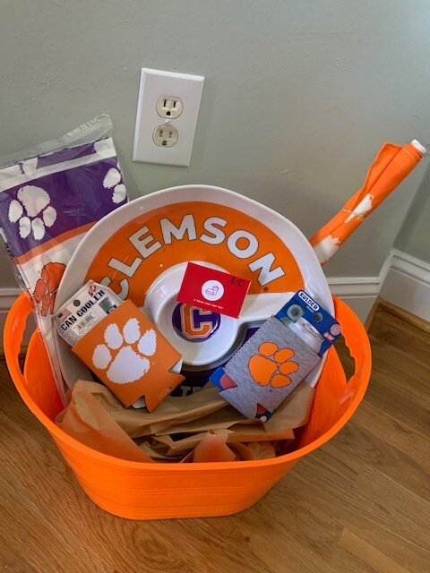 """""""CLEMSON ALL THE WAY"""" BASKET   You'll look as prepared as our team is with your car swag, table cloth, koozies and platter. Not to mention you'll be ready to host the next amazing tailgate with this $50 gift card to Chick-fil-A to get your chicken minis or nuggets.  DONOR: 2nd Grade Classes VALUE: $115"""