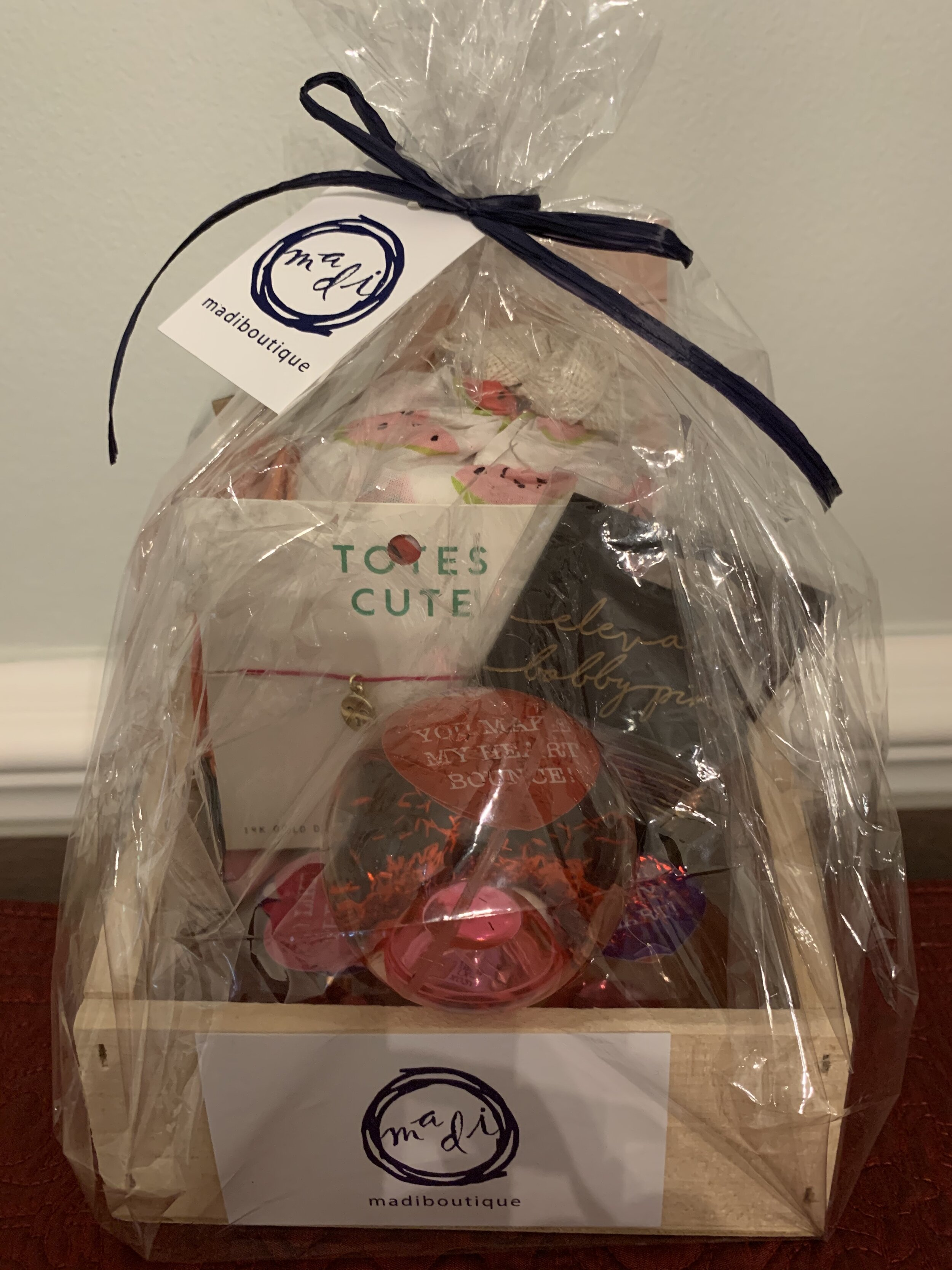 GIRLY GIFT BASKET   This gift basket is sure to make your girl swoon with delight! Included are watermelon PJ pants (sz L), (3) heart bouncy balls, Emoji necklace, hair pins, key chain and web book.  DONOR: MADI Boutique VALUE: $115