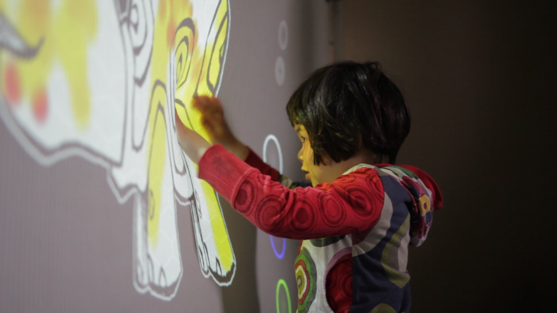 Ara playing with the  sensorySURFACE | stretchCOLOR  prototype, where pressure applied to the 2D textile determines the color being projected onto the surface.