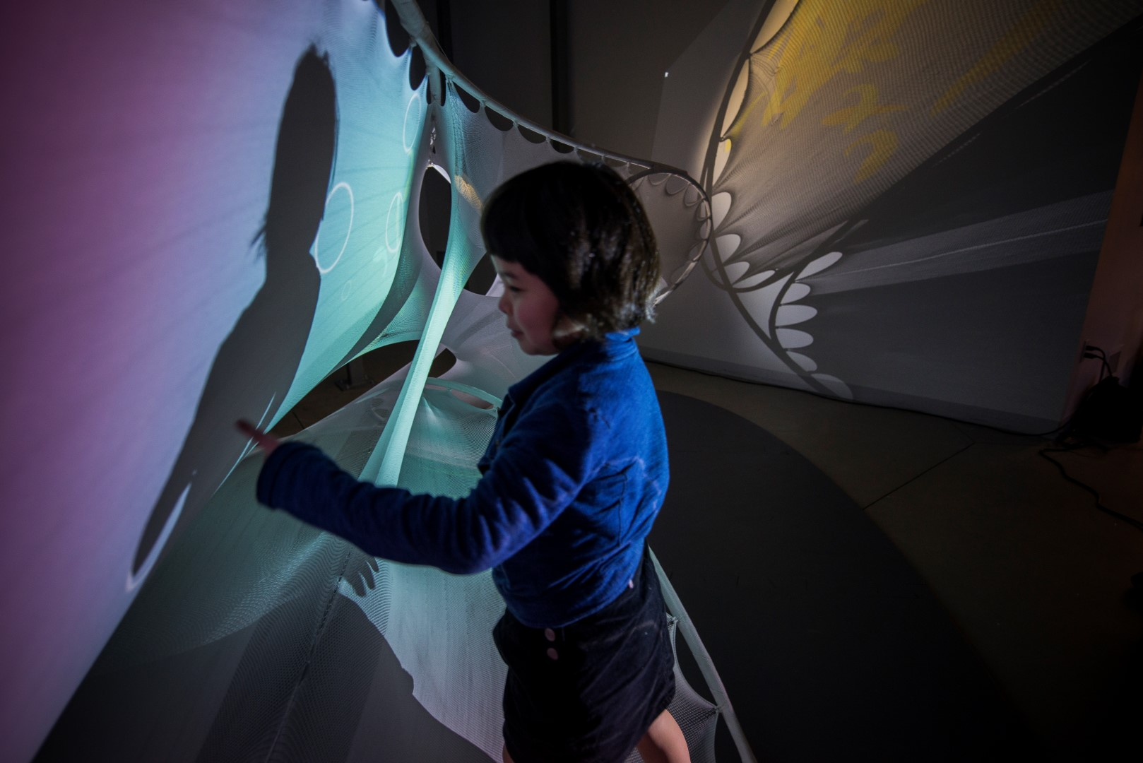 Ara playing with the  sensoryPLAYSCAPE | stretchSWARM  prototype which combines textile-hybrid technology with an interface for interacting with swarms of fish.