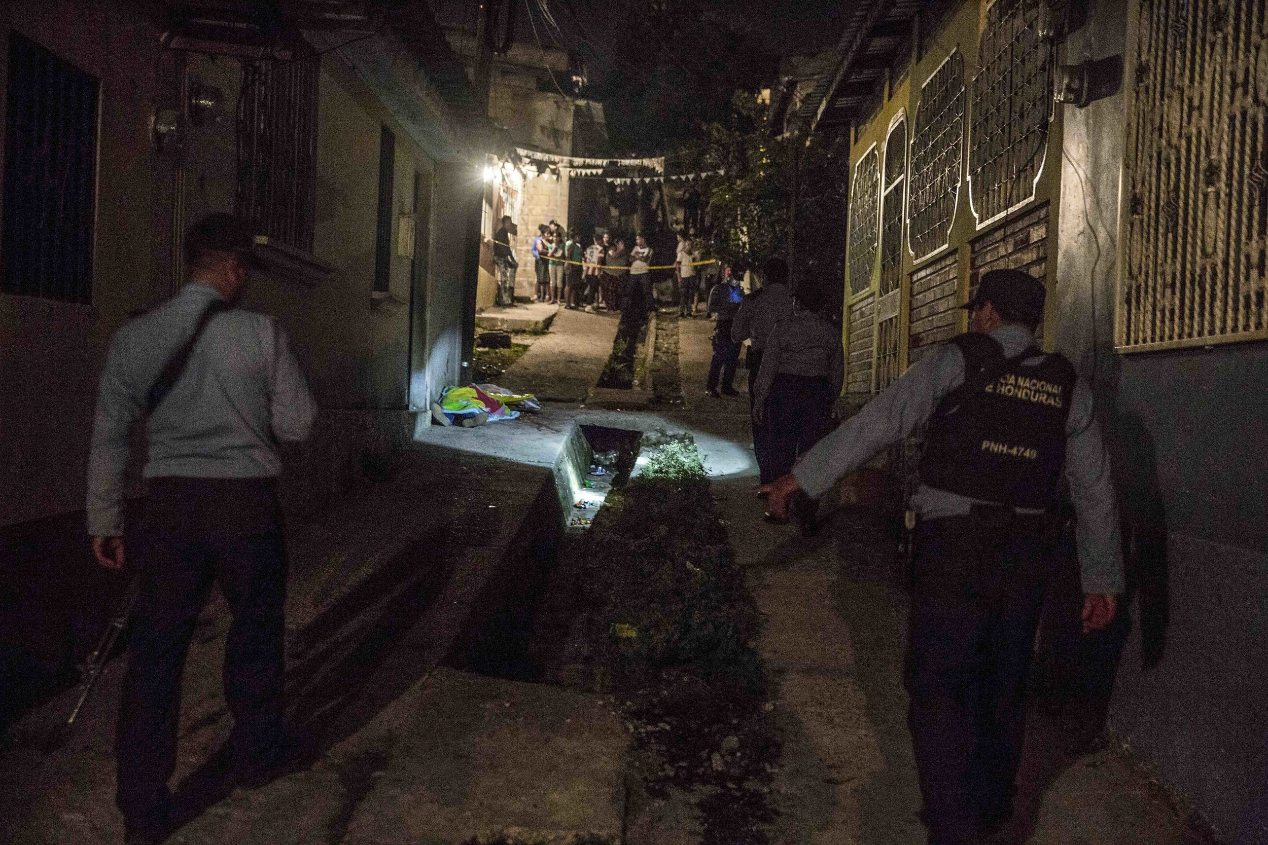 Honduran police officers guard the corpse of a woman, who was killed along with three others and a boy, apparently as a result of drug-related issues, in one of the districts of the capital Tegucigalpa.