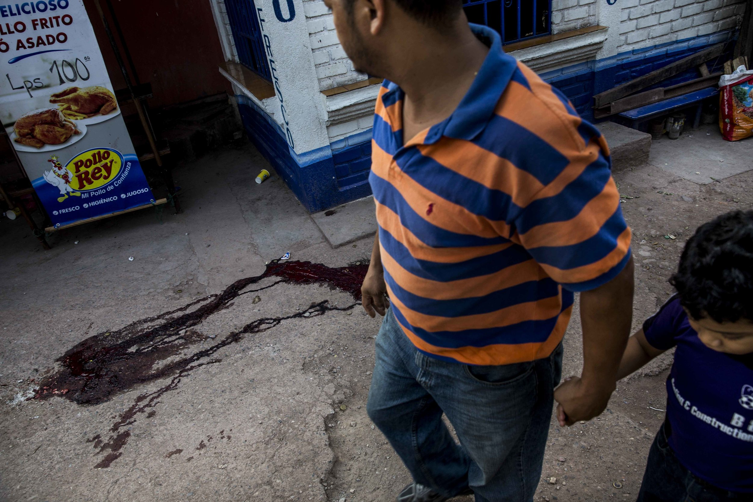 Father and son walk by next to the pool of blood left by the dead body of Edwin Amador, 20, murdered in cold blood in the streets of the Suyapa district, Teguciaglpa, capital of Honduras.