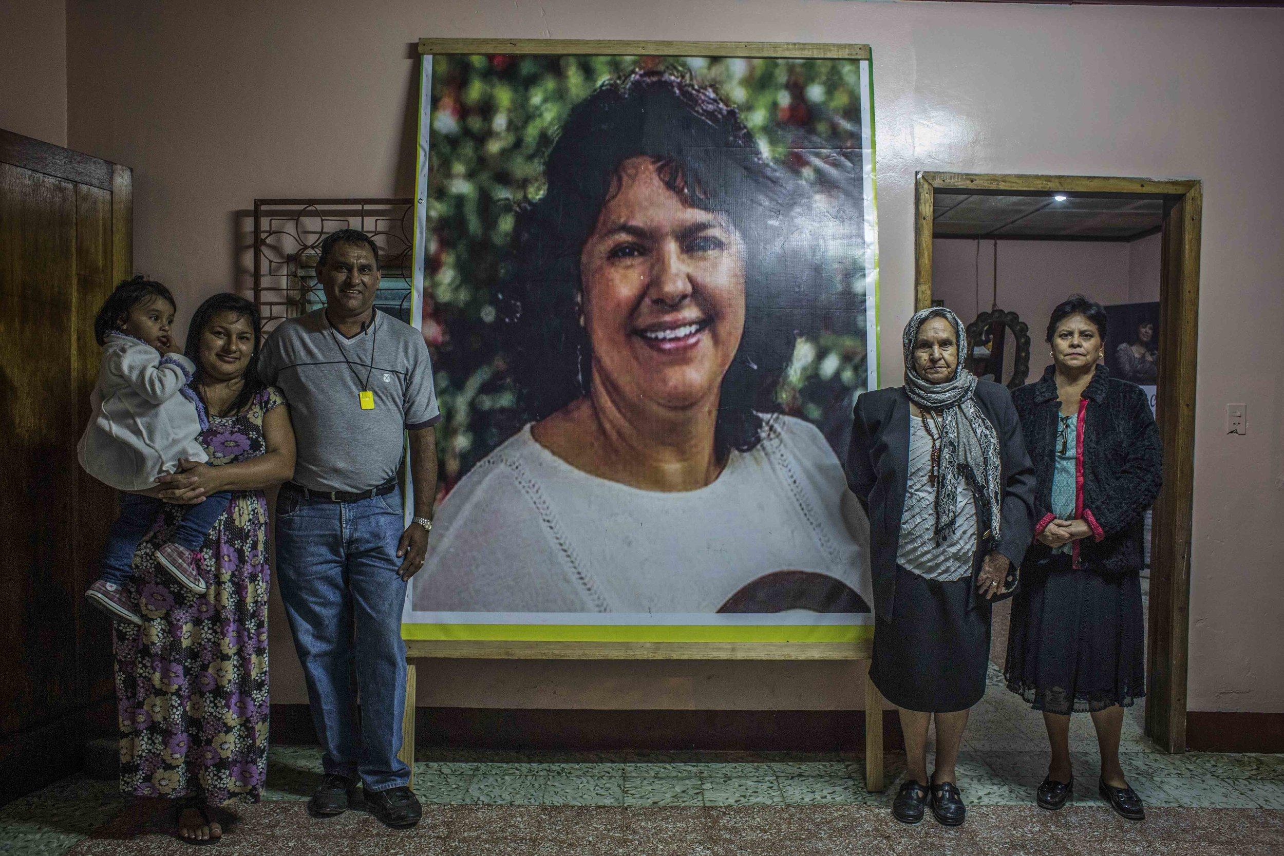 The family of Berta Caceres, mother's sister and brother-in-law with her daughter, posing next to poster of Berta , affixed at the entrance of the family home, in the city of La Esperanza, Honduras.