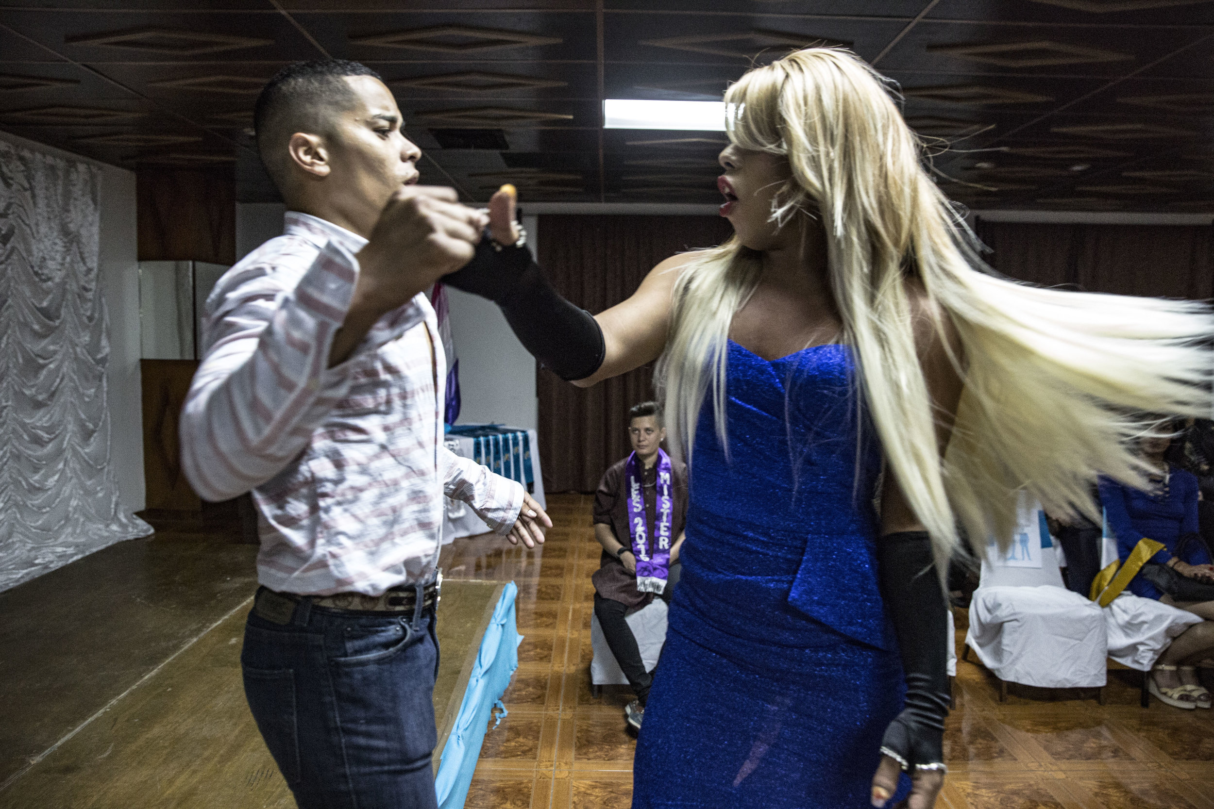 """Darwin does his show at the beauty contest """"Miss Arcoiris"""". Arcoiris in spanish means """"rainbow"""" and it is an organization that advocates for LGBT rights in the country. His brother Marco, also known as Shirley, was an activist of the organization as well."""