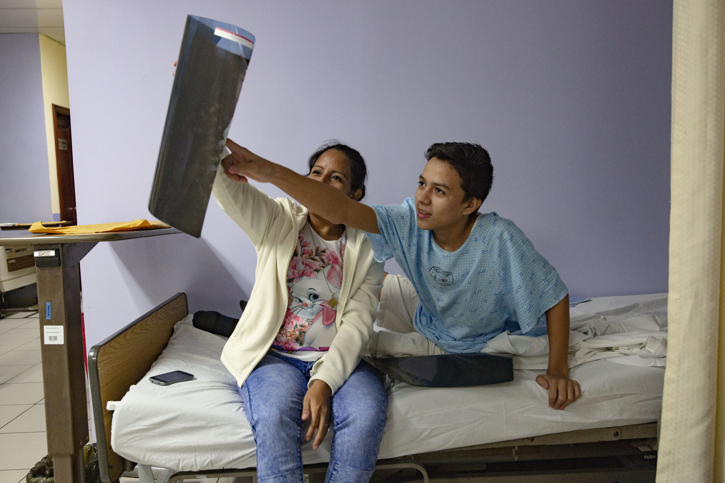 A boy and her mother look at the results of an ultrasound before his operation the following day at the Ruth Paz hospital in San Pedro Sula, Honduras.