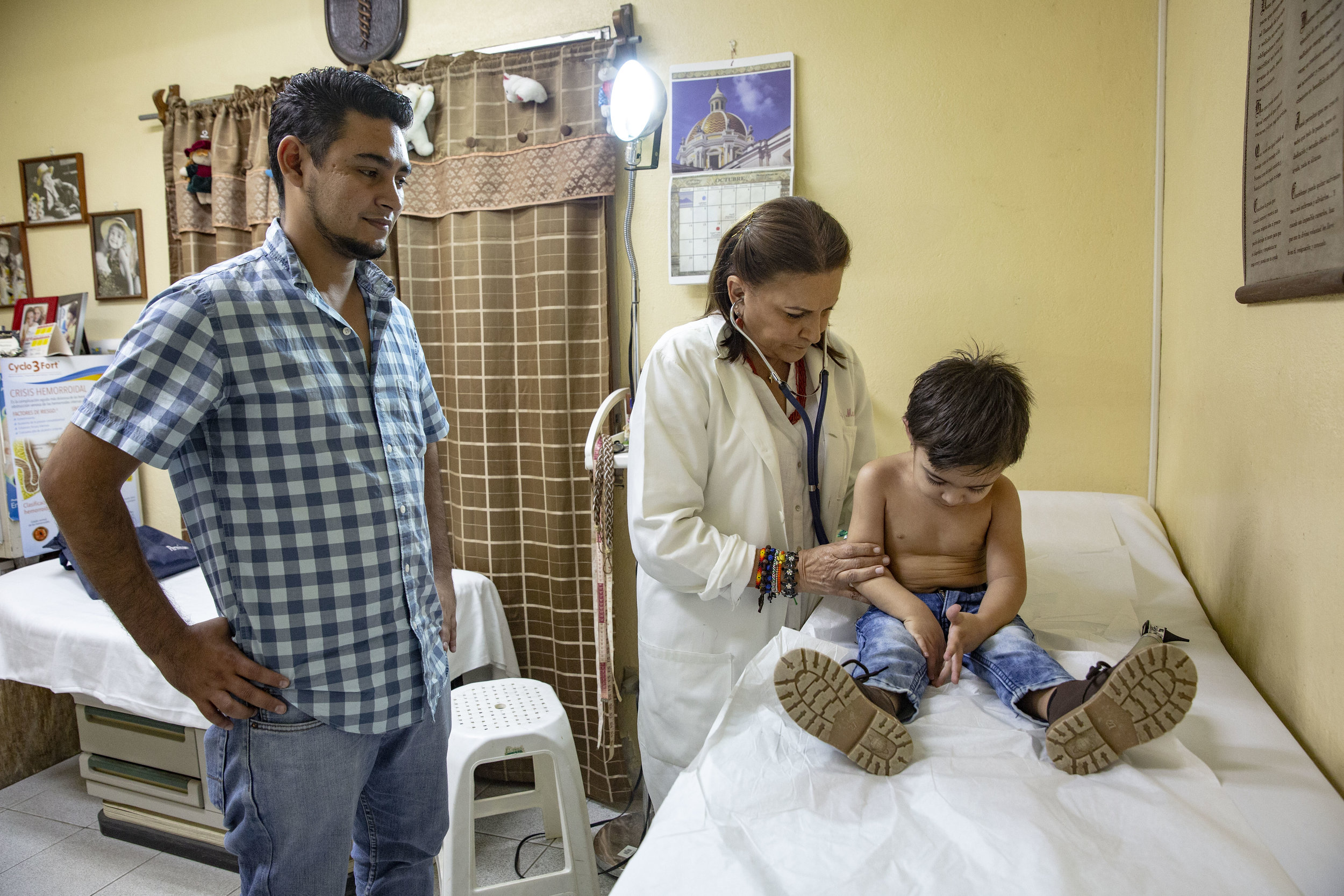 Doctor Madrid visit a child while his father attends, at the ruth Paz clinic in San Pedro Sula, where various services are provided:various services: general medicine, dentistry, and orthodontics.