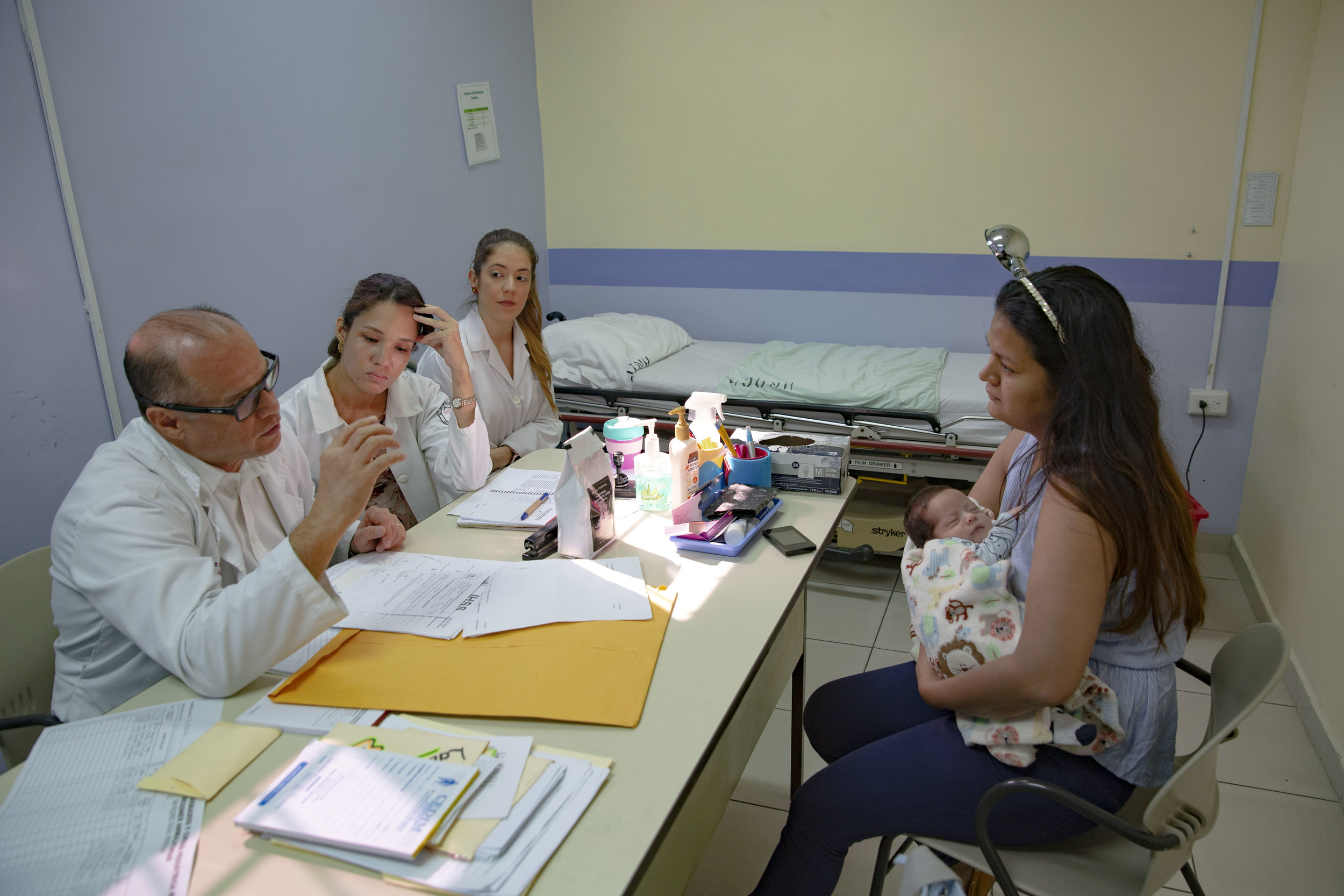 Doctor Craniotti, head of the Ruth Paz hospital in San Pedro Sula and pedriatic surgeon specialized in anorectal disfunctions speak to a mother and her little baby alongisde his assistans.