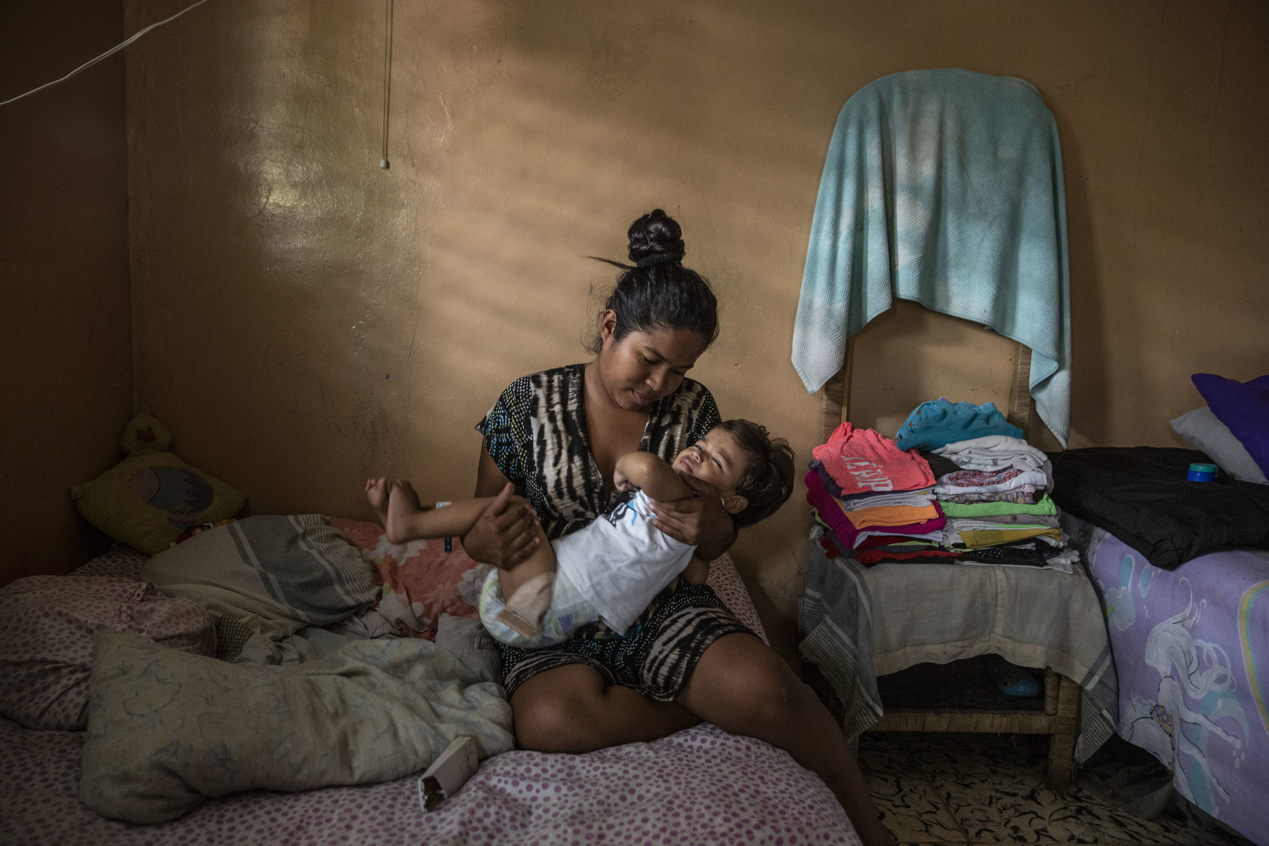 Claudia in her home holds his one year old child, Ricardo Lopez who just returned home from a nine hour long surgery at the Ruth Paz hospital in San Pedro Sula,, conducted by Dr.Craniotti, chief surgeon and specialist in anorectal disfunctions.