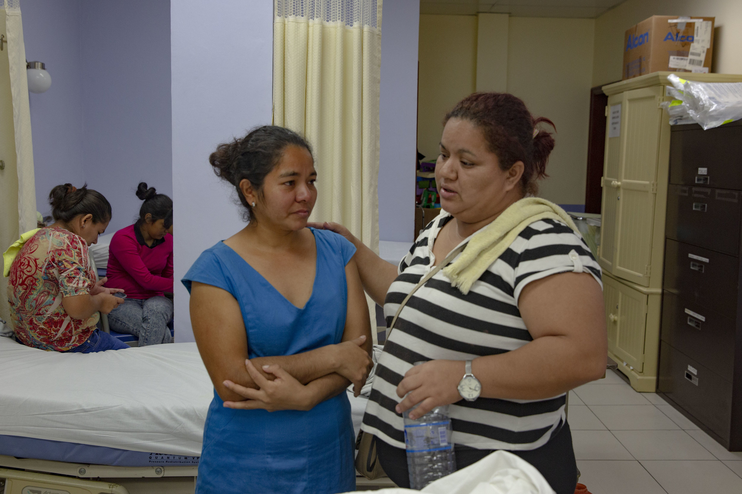"""The mother of Franklin Misael Vasquez Lopez, 17, here at his bedside at the Ruth Paz hospital in San Pedro Sula, Honduras. Franklin broke his femur when he was on a motorbike with his friend. """"I brought him to the public hospital, they just gave him a lot of painkillers and that's it, they didn't really treated him for 21 days. When his skin started to become yellowish and his leg extremely swollen then I brought him here at the Ruth Paz hospital""""."""