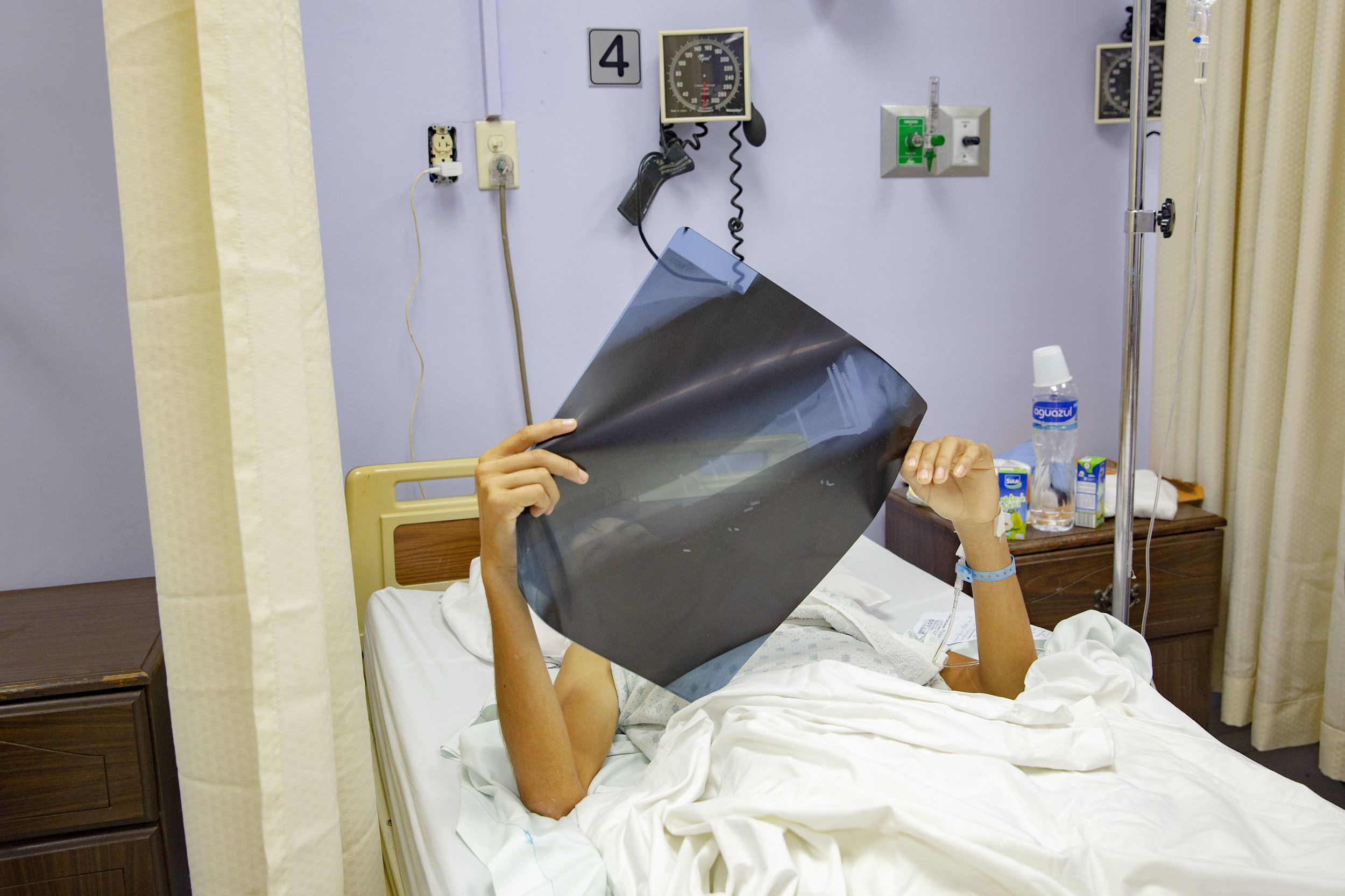 """Franklin Lopez, 19, lies in a bed looking at the results of an ultrasound exam at the Ruth Paz hospital in San Pedro Sula, Honduras. He broke his femur when he was on a motorbike with his friend. """"We were just playing, it was an accident"""" he says, visibly in pain. After the accident he spent twenty-one days at the public hospital without being treated for his fracture, then his mother took him to the Ruth Paz hospital an he was operated three days after his arrival."""