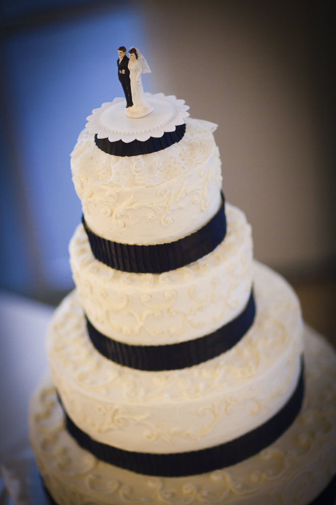 A four tiered round classic cake for their wedding reception with traditional topper