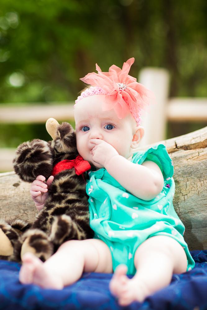 A newborn and her fuzzy giraffe