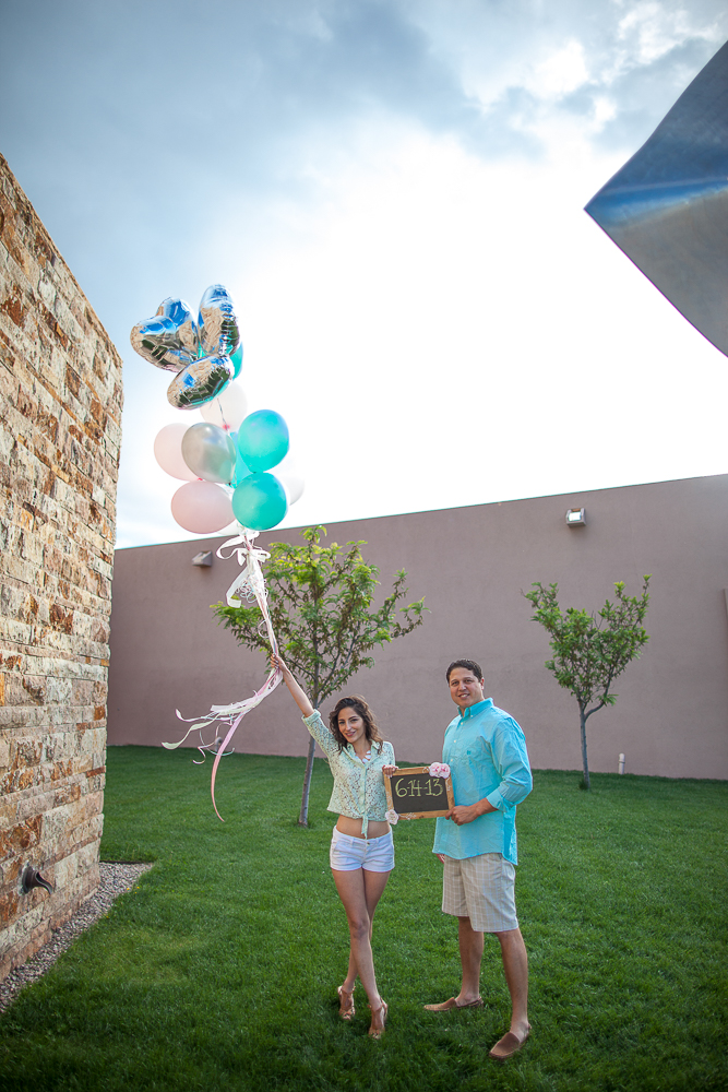 JC & Gaby holding both balloons & a chalkboard in their complementing colors! - Love Springs Studios