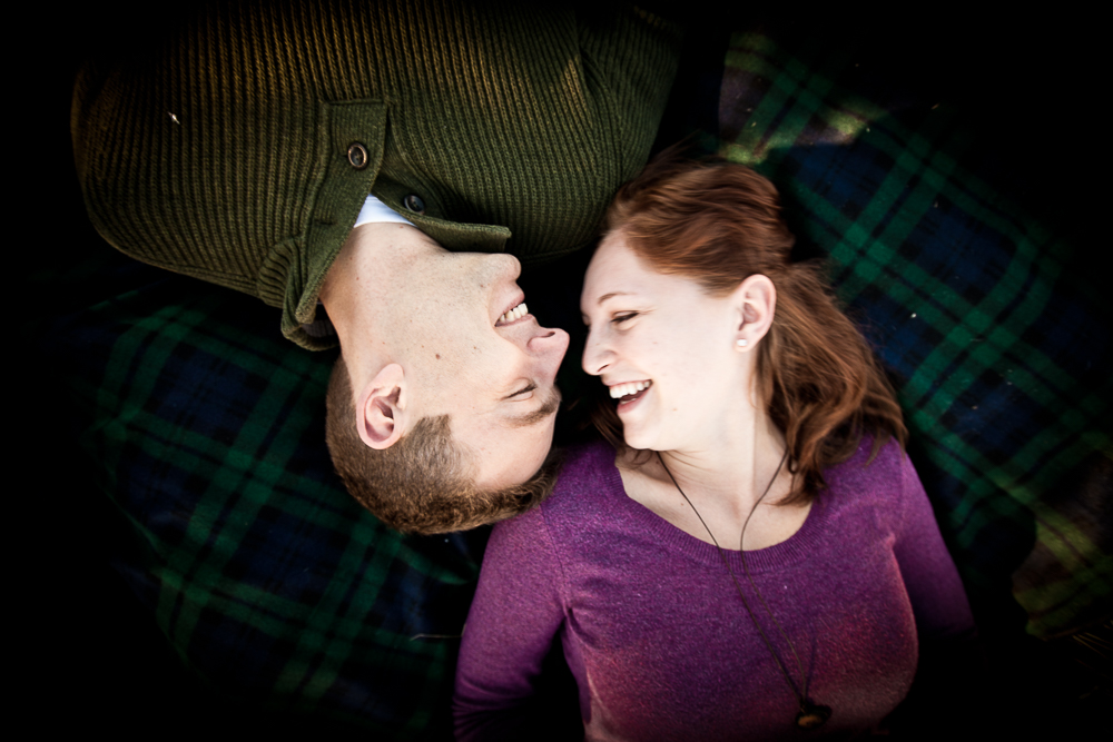 Michael & Jessica laying on a plaid picnic blanket. - Love Springs Studios