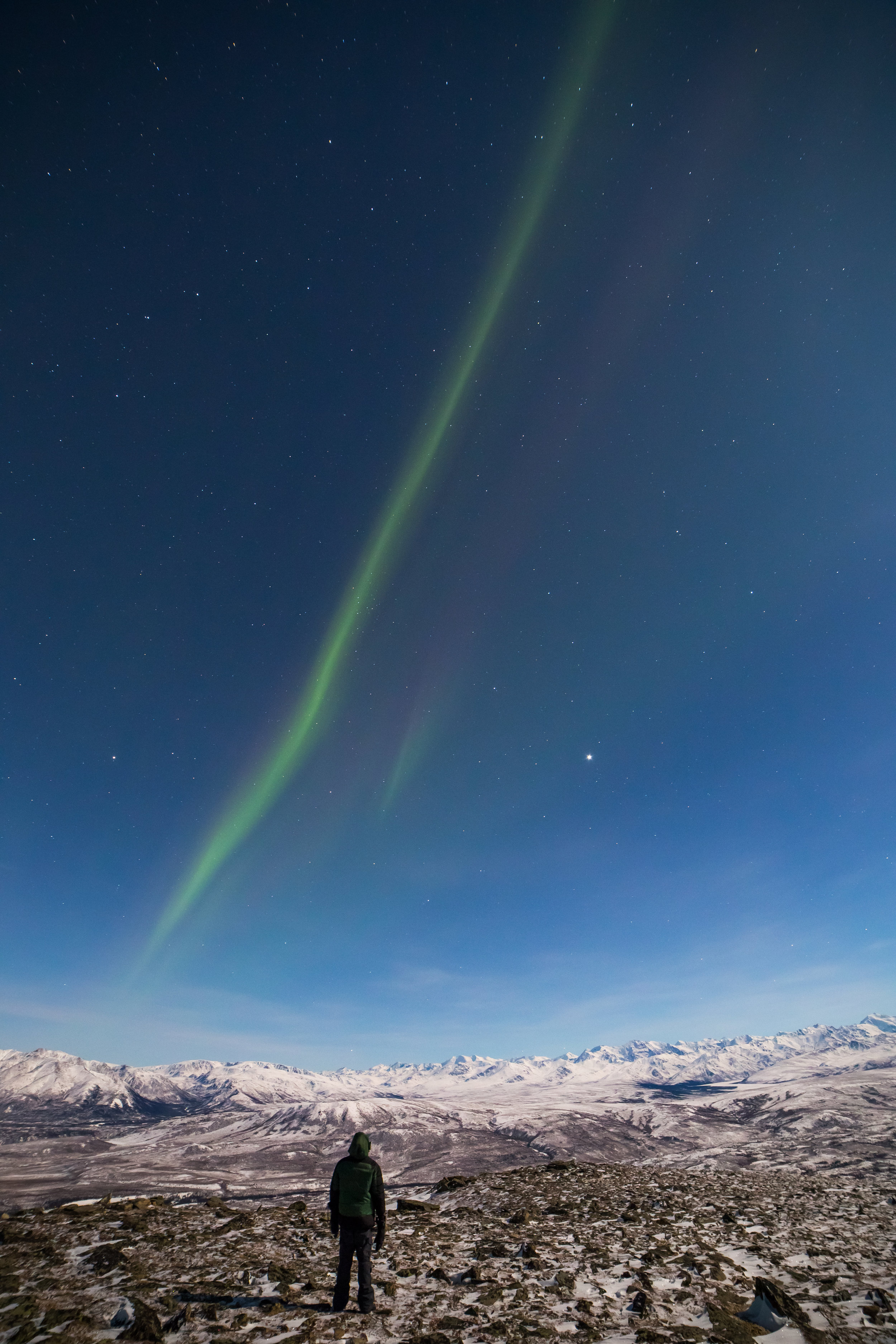 A band of aurora hangs over the Alaska Range. The bright object is Jupiter.