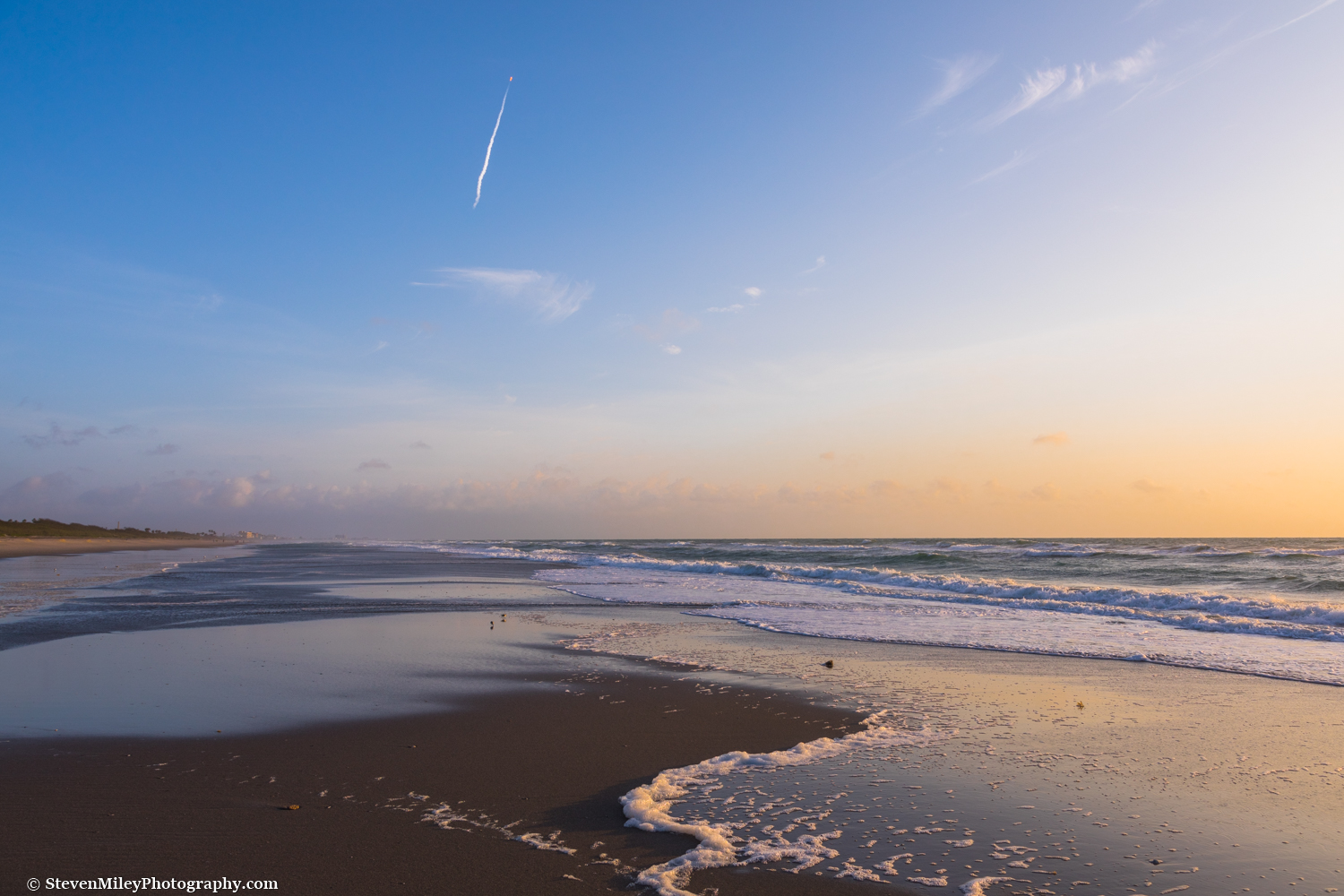A SpaceX Falcon 9 rocket shoots into space above a lonely section of beach near Patrick Air Force Base.