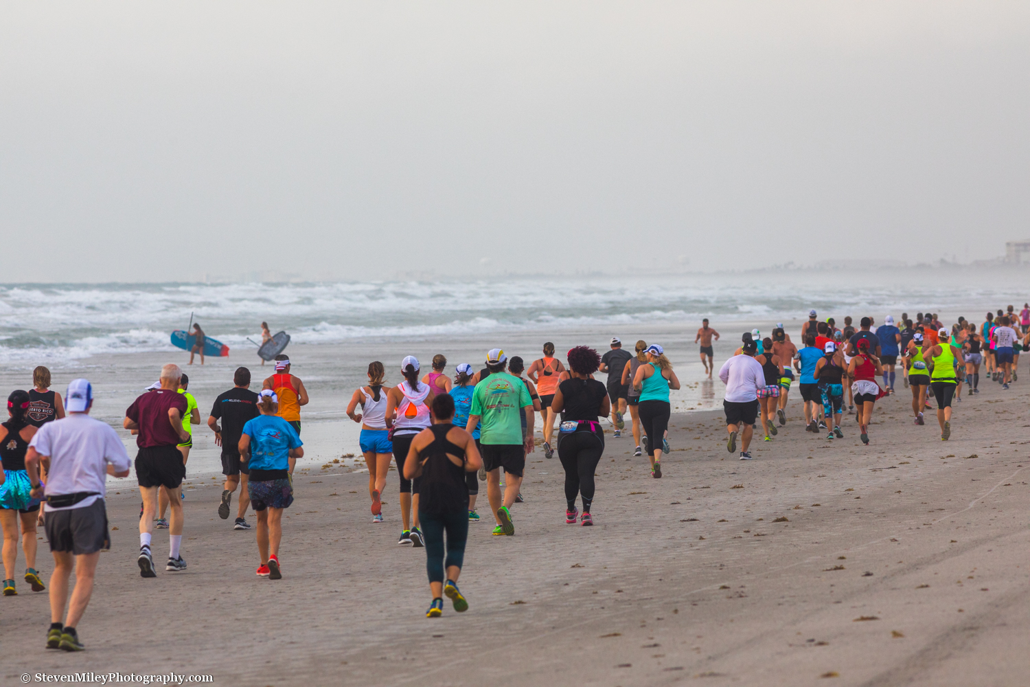 A pair of paddleboarders sneak through a long line of runners participating in the U.S.A. Beach Running Championships. Cocoa Beach, FL.