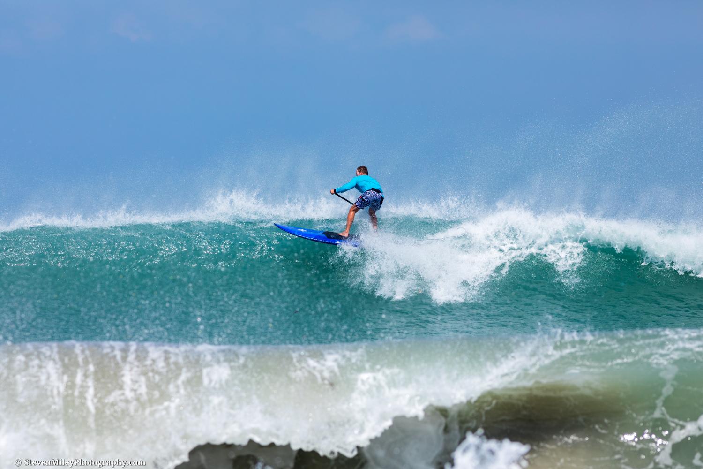 Paddleboarder riding big surf in Satellite Beach, Florida.
