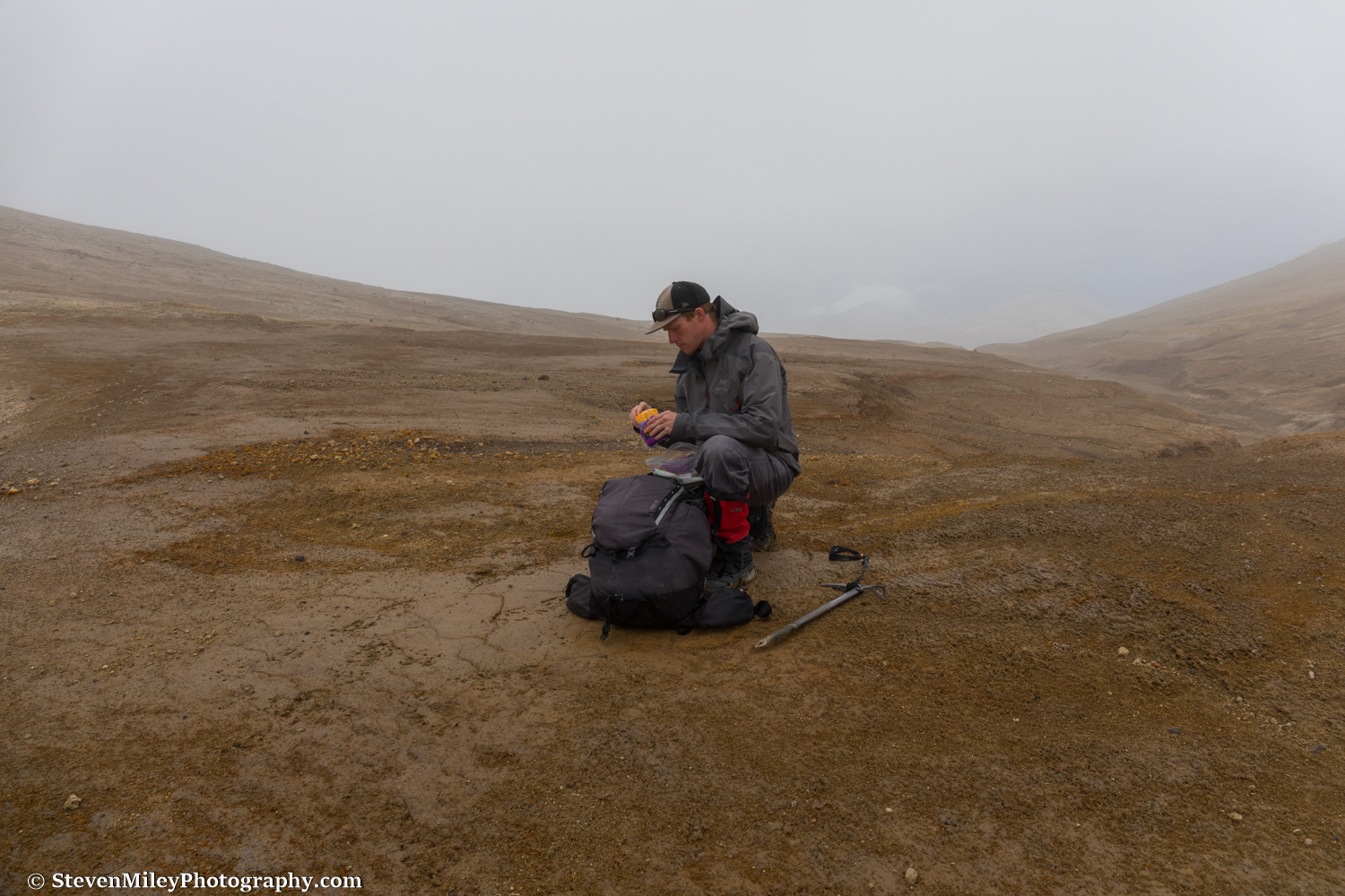 Pausing for some cheese at the pass between Trident Volcano and Mt. Katmai. The rounded top of Broken Mountain is barely discernible through the clouds to the right of my head.