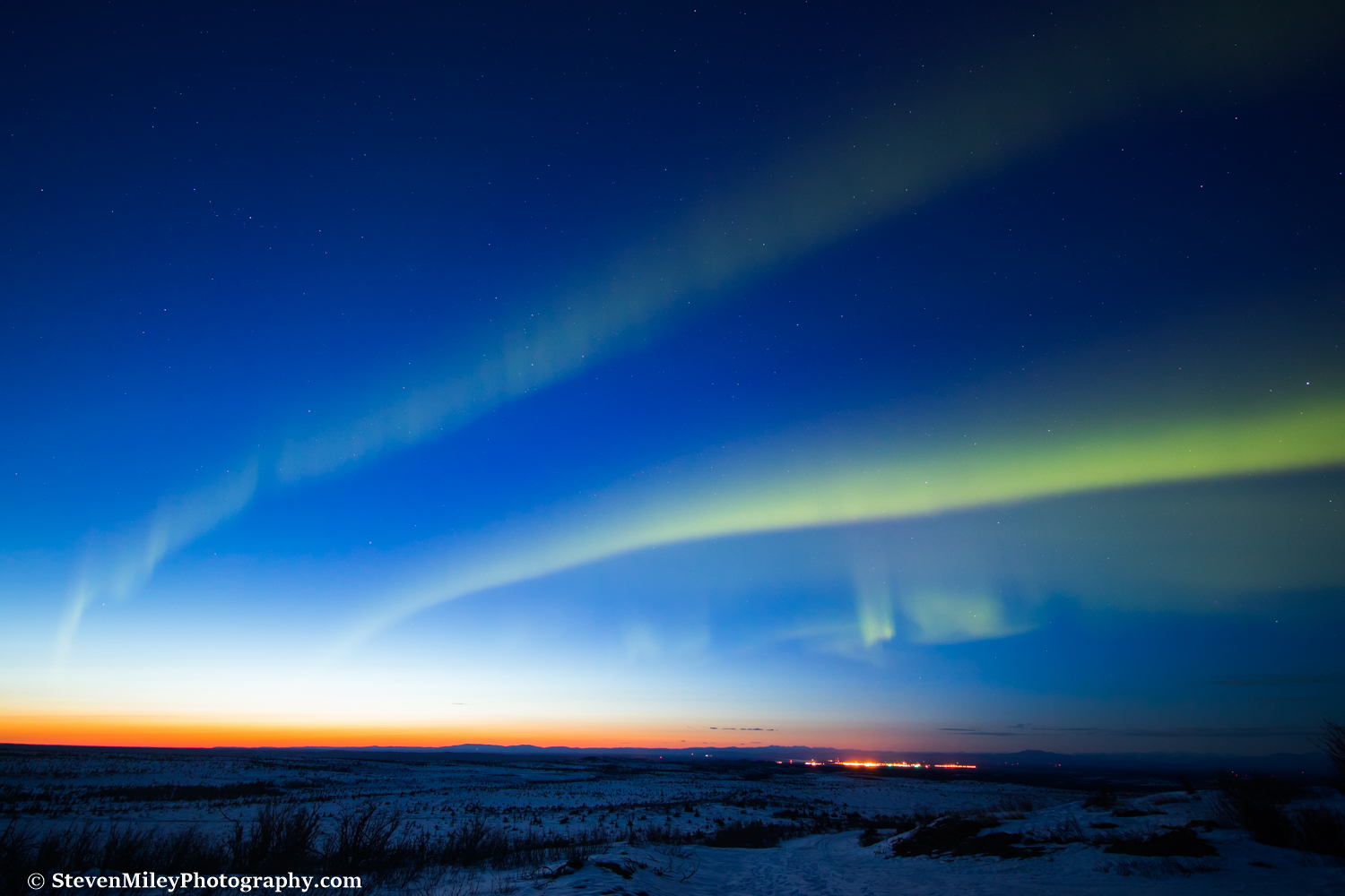 Aurora borealis dancing during twilight above the lights of Fort Greely.