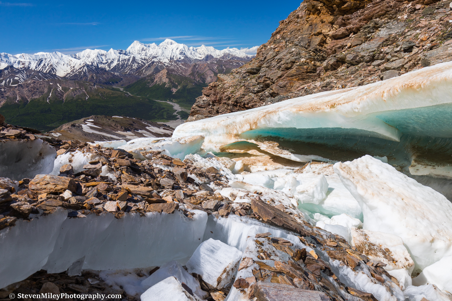 """Snow-turned-to-ice melts along """"Grizzly Creek"""" with the Hayes Range in the background."""