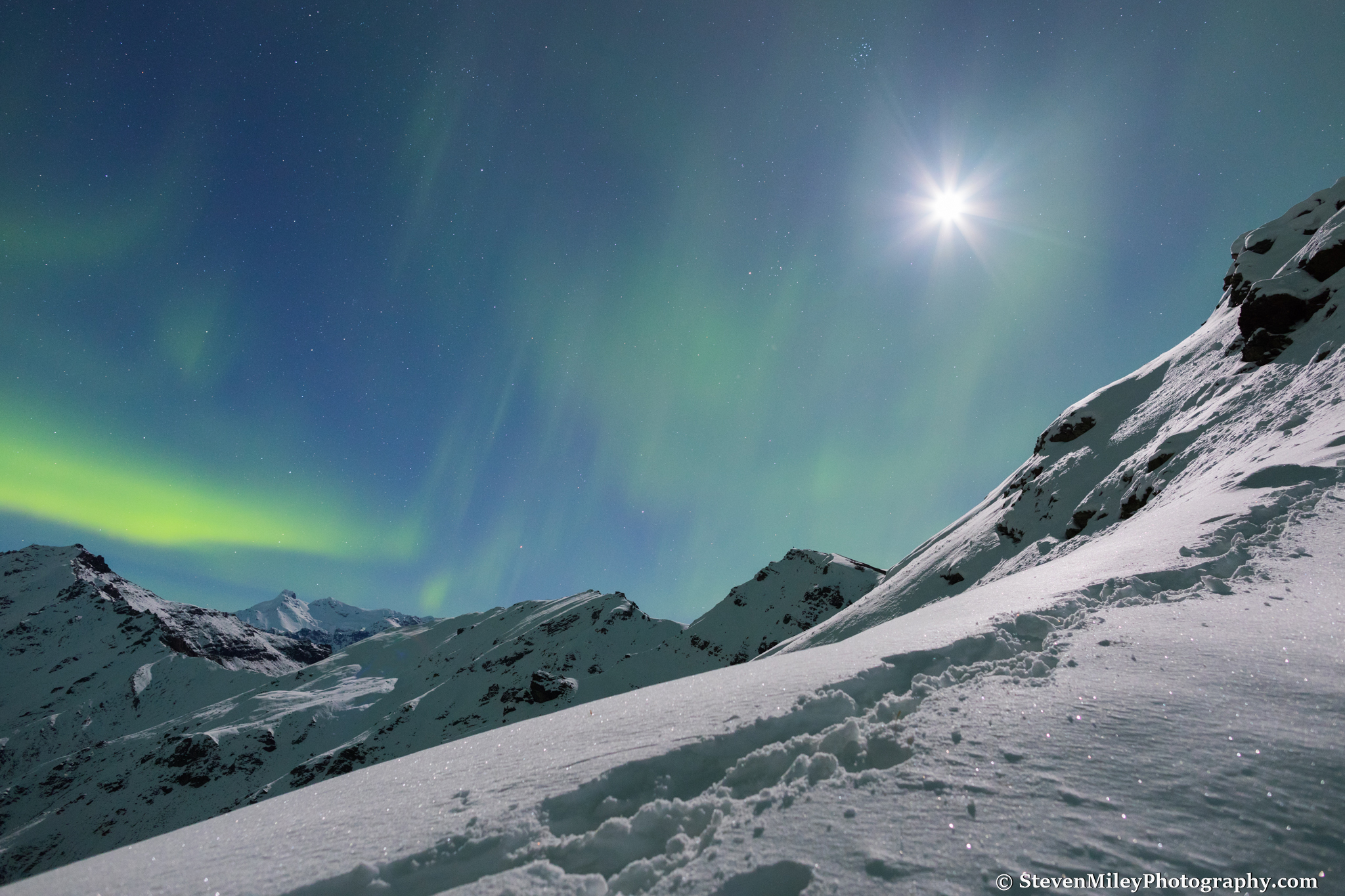 Aurora and the moon in the sky with our tracks on the spur in the foreground. Grant is visible as a small black dot on the rightmost false summit.