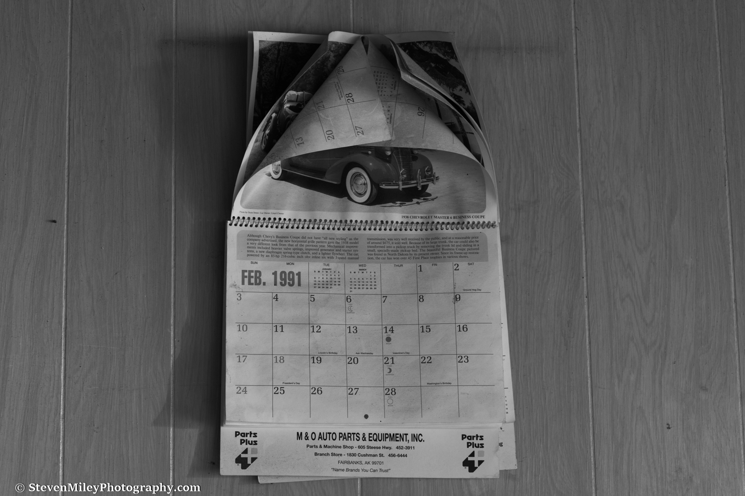 The 1991 calendar still hanging on the wall of the office was my best indication of when the shop last operated. I picked up one of the work orders scattered on the floor and the date entered was 1983. A soiled mattress with blankets in an adjacent room suggests one or more vagrants inhabited the building in the past, but not recently. Another room with a ragged couch and chair may have been a waiting area, but it's now missing a wall and opens directly into the junkyard.