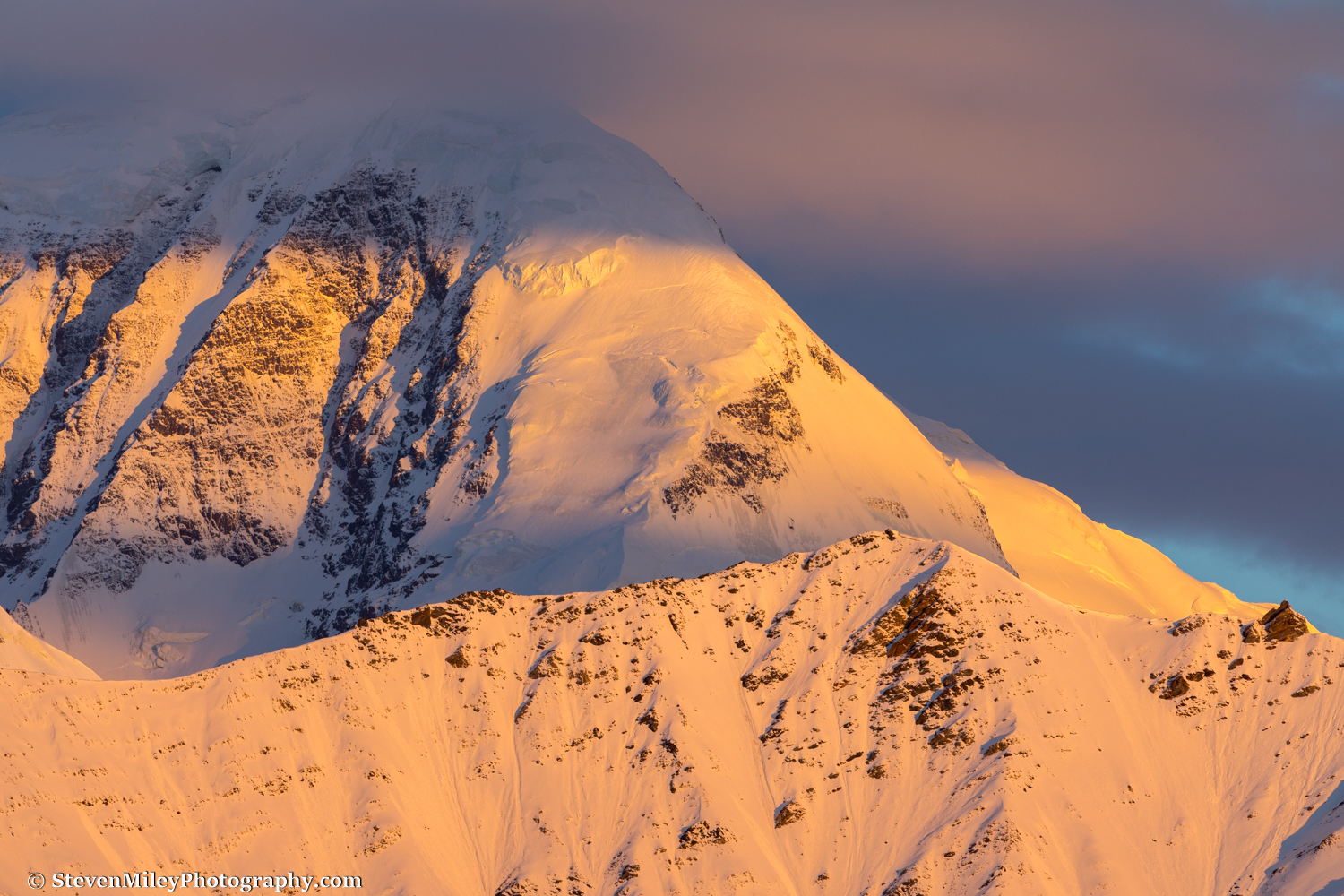 Sunrise on Mount Moffit's southeast face, viewed from a pass near McGinnis Glacier.