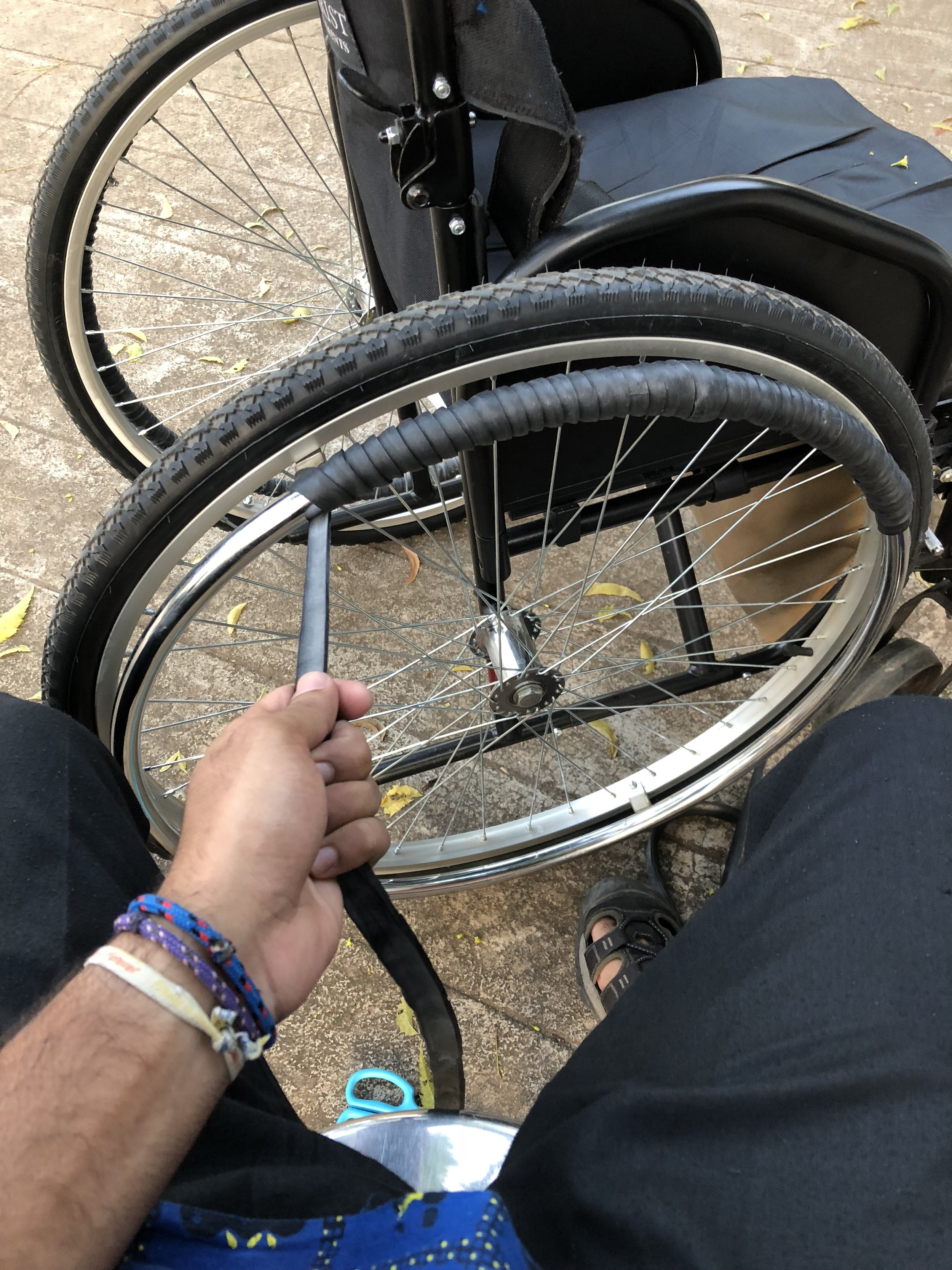 Wheelchair adaptation using old bike tire inner tubes to increase grip while self-propelling