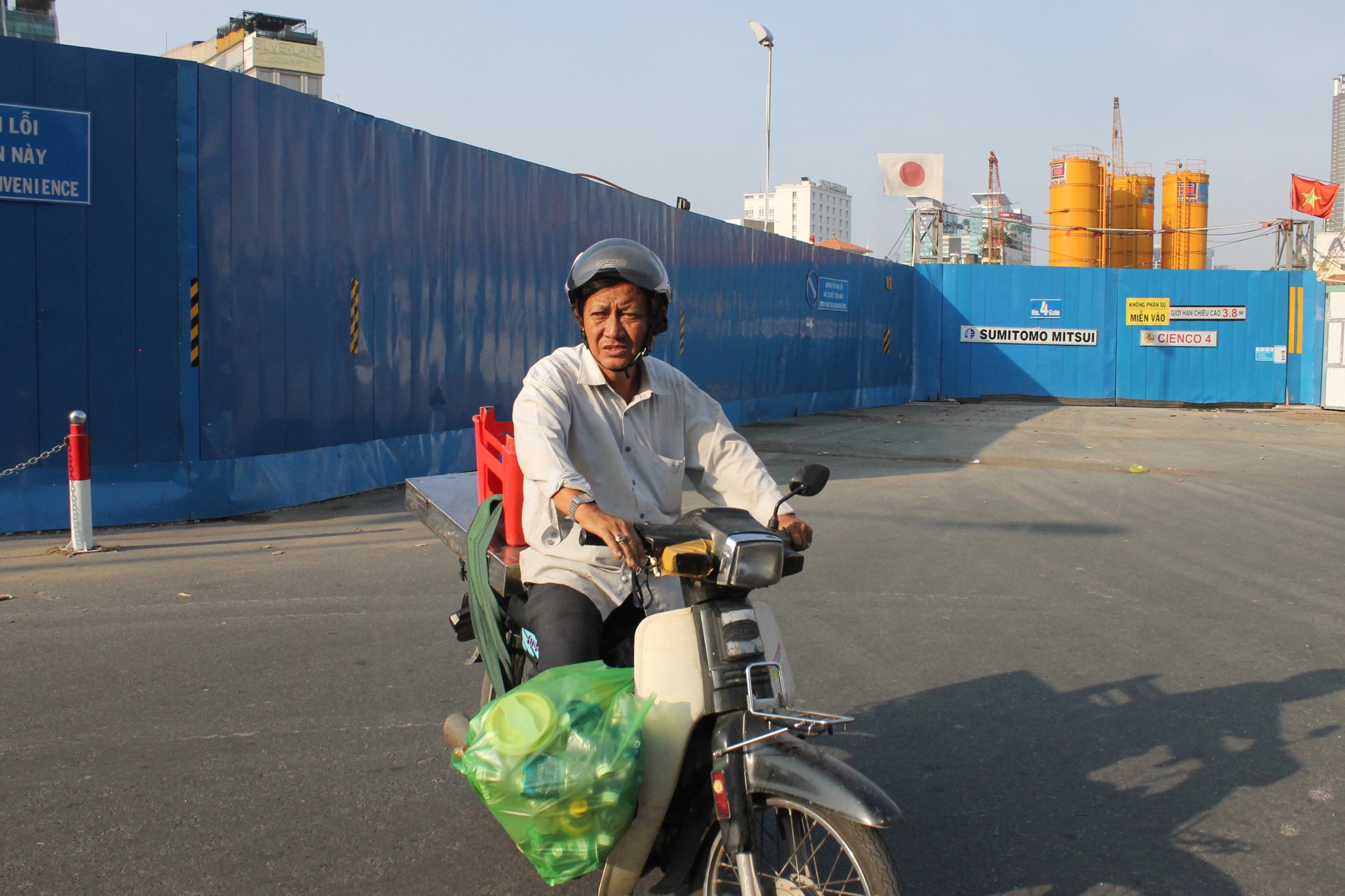 A man prepares to face the ruthless traffic in Ho Chi Minh City. Pictured in the backdrop is one of many construction sites in this metropolis.