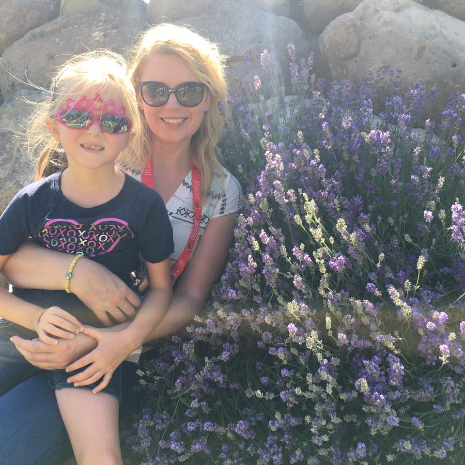 Jess with her friend Lainey sitting next to a lavender plant at the Young Living farm in Mona, Utah.