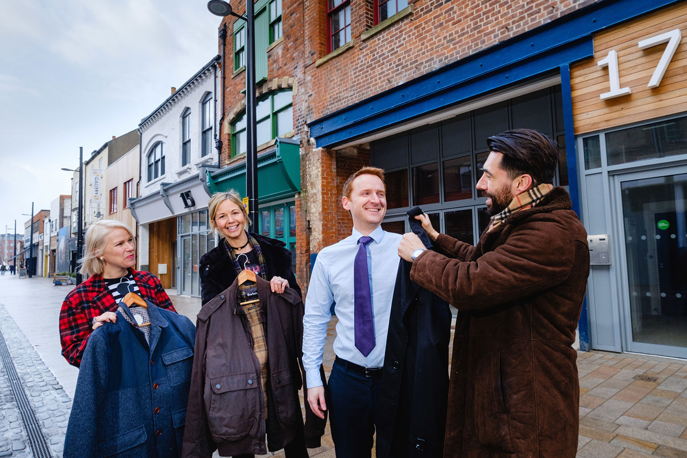 Owner Riccardo Seaton sizes up Wykeland's Tom Watson for a classic Burberry coat from Poorboy Boutique's range, watched by Angela Seaton and Caroline Pendleton, right.