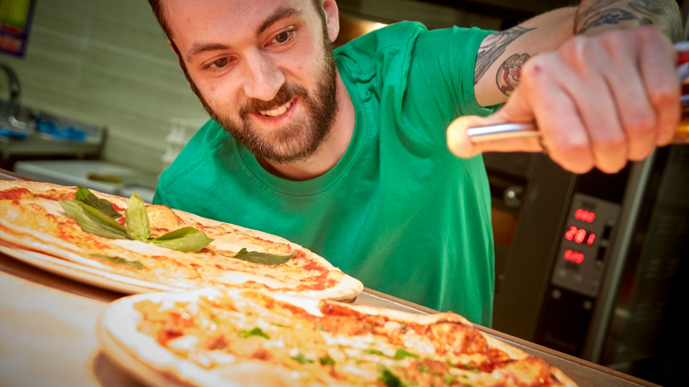 Head Chef Tom Lynch prepares mouth-watering meals for Buca di Pizza diners.