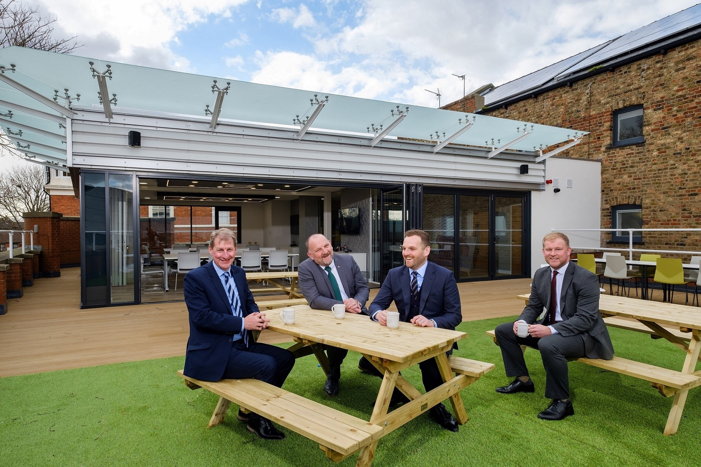 "Hugh Rice Chairman Mike Rice, second left, and Sales and Marketing Director James Rice, third left, with Wykeland's David Donkin, left, and John Gouldthorp on the rooftop terrace of their new offices, which features a new-build ""pod"" used for meetings and events."