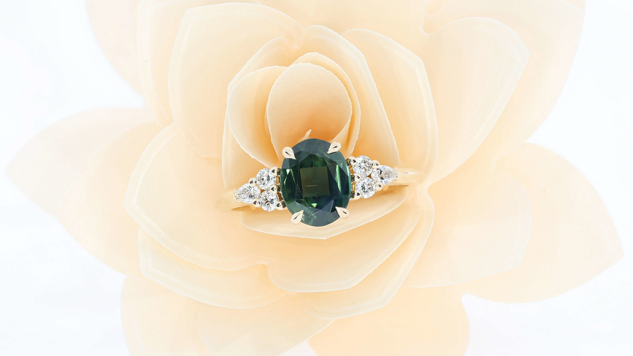 A bespoke engagement ring, using a green centre sapphire, and round and pear shoulder diamonds, set in 18k rose gold