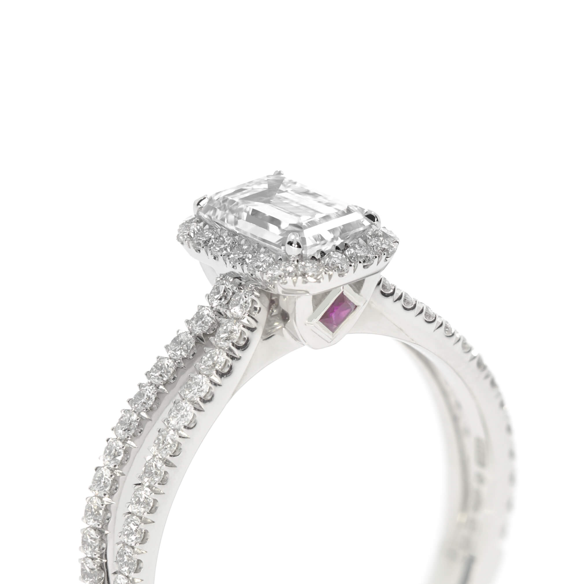 A more intricate design, using an emerald cut centre diamond and split scallop set band, with the sweet touch of a small ruby