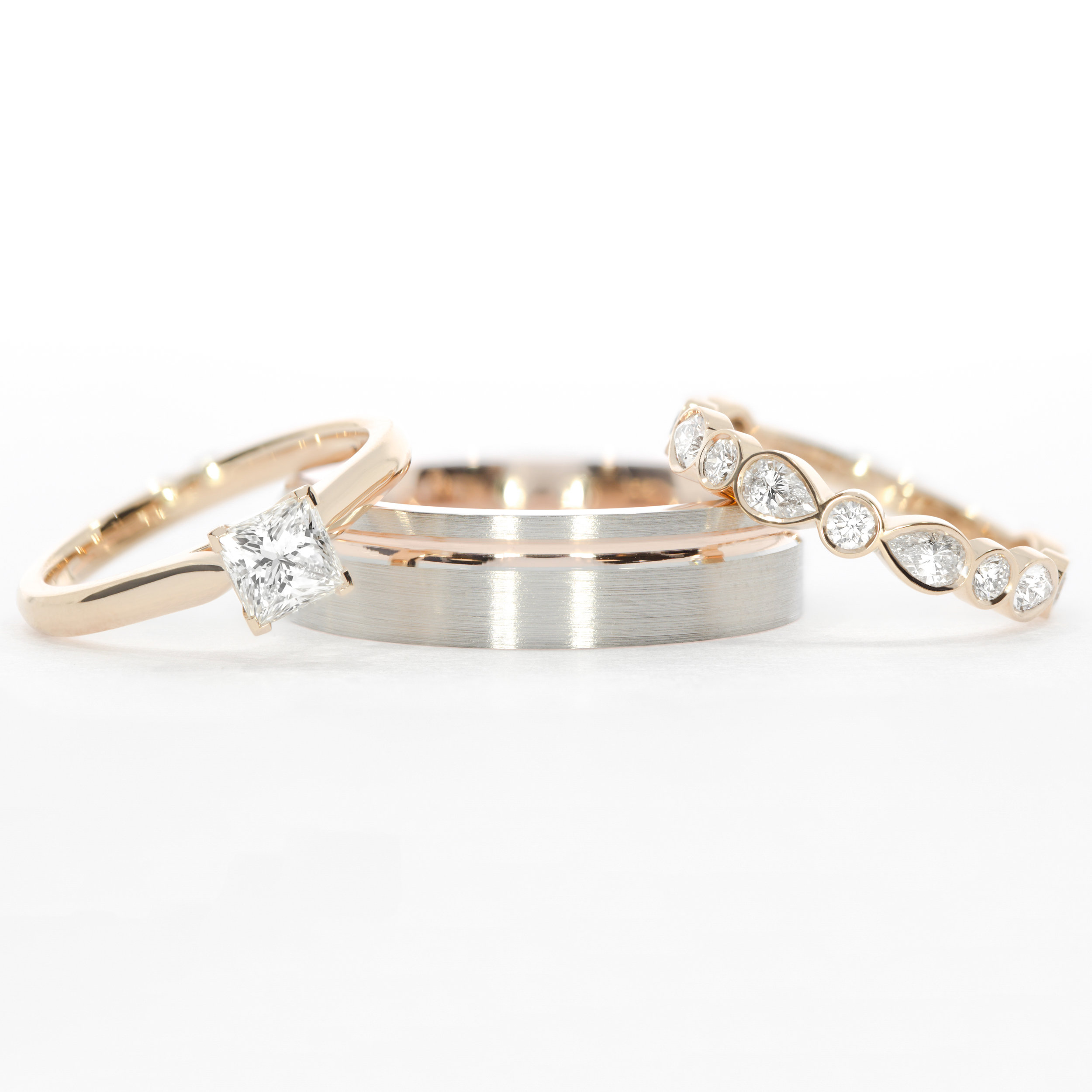 Bespoke trio:  De Carlo princess cut solitaire ,  Men's platinum & rose gold wedding band  and  Women's Montez pear & round diamond wedding ring
