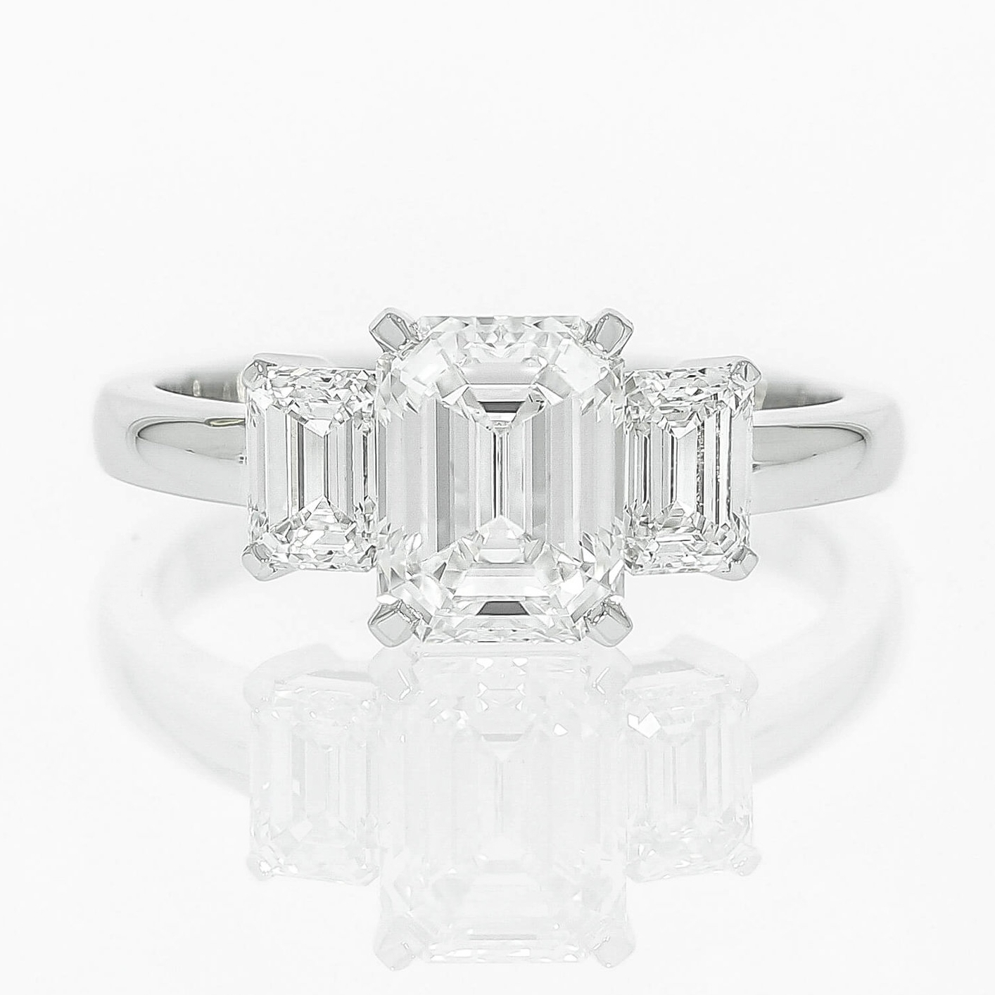 This emerald cut diamond trilogy engagement ring is crisp & modern, by Queensmith