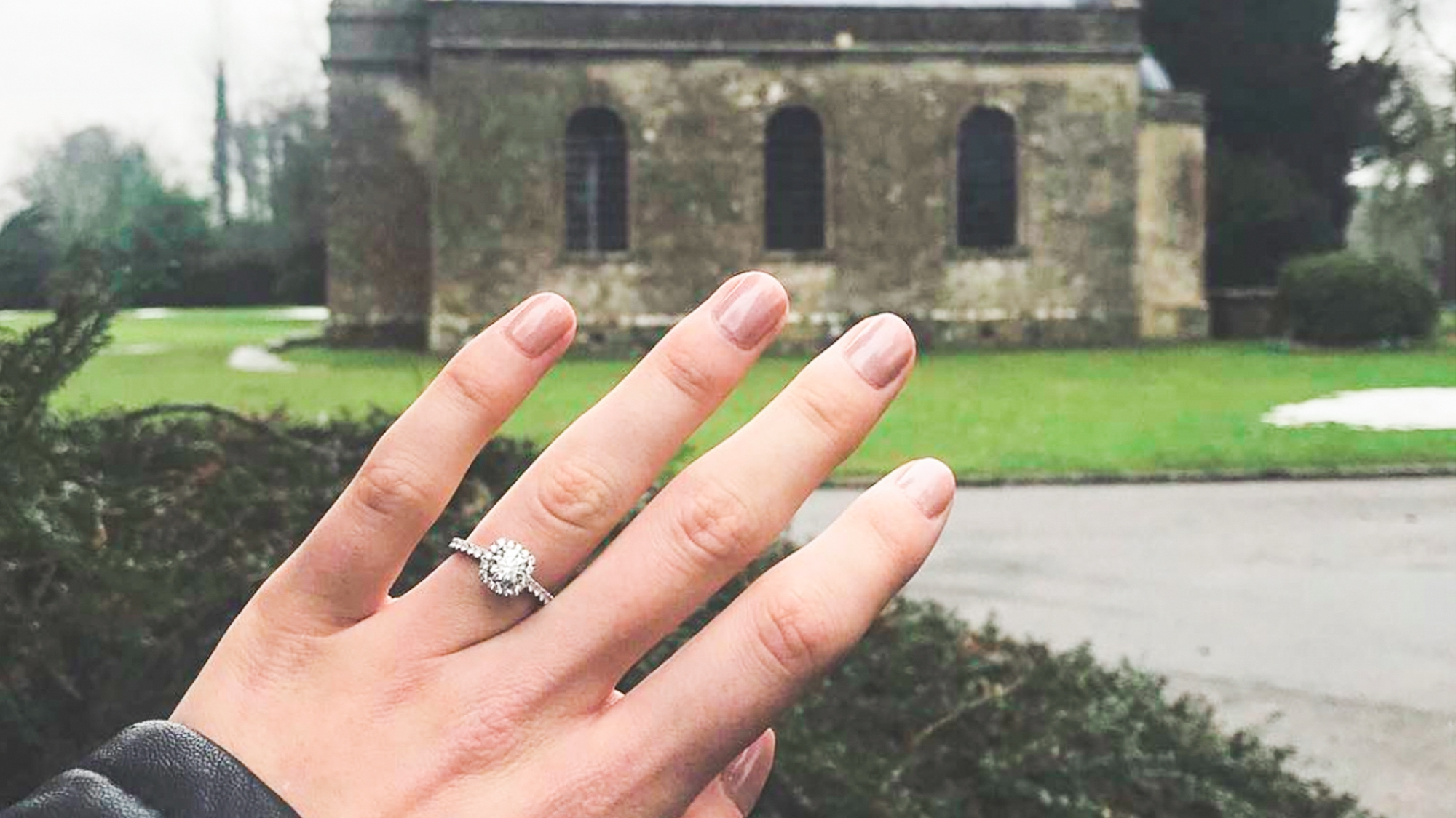The  Classic Kelly  engagement ring, as worn by Queensmith client Becca, outside the picturesque Babington House Chapel