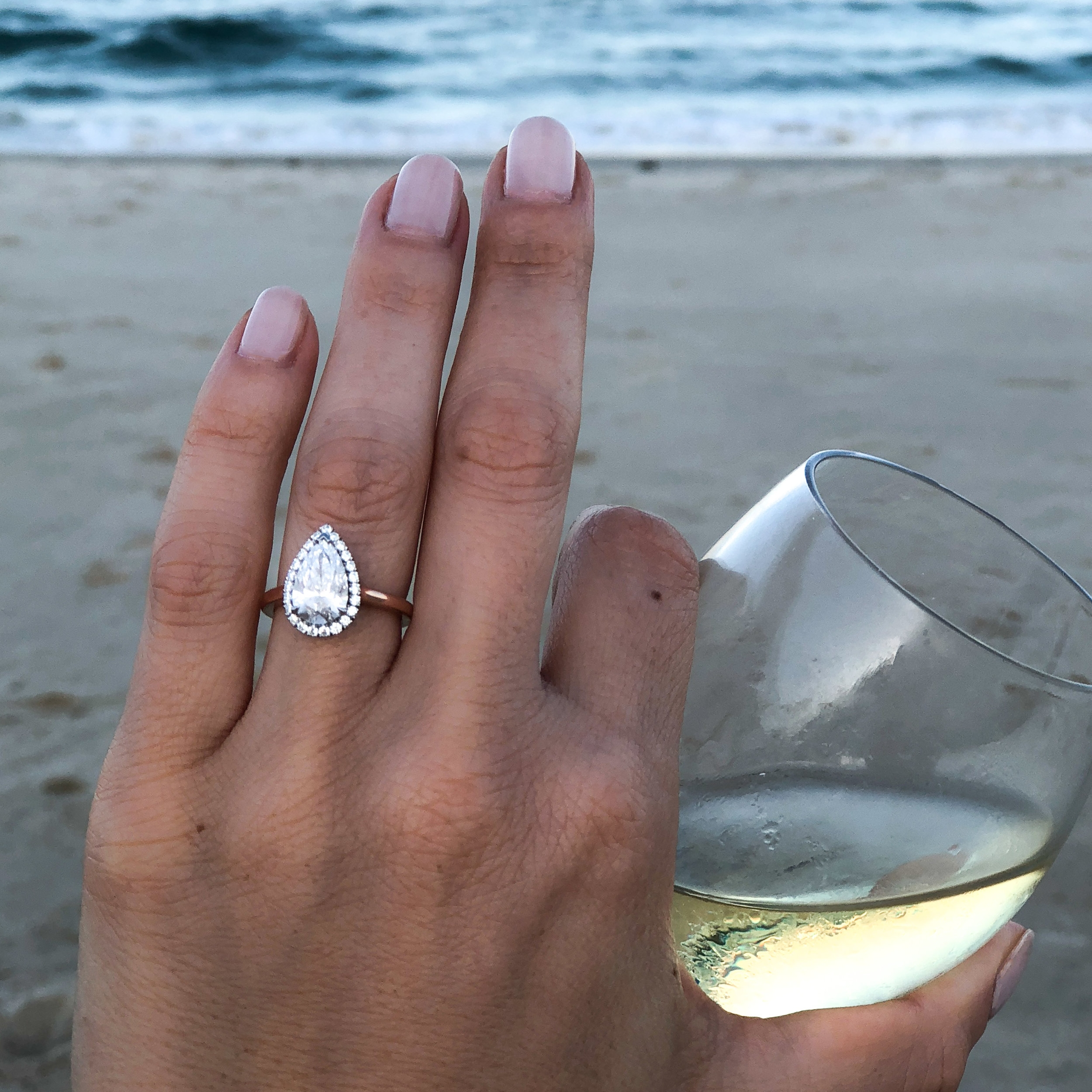 A  bespoke pear diamond halo  engagement ring, by Queensmith, on a blissful Australian beach