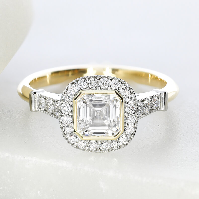 A bespoke engagement ring commission, featuring a bezel set Asscher cut, with milgrain detailing