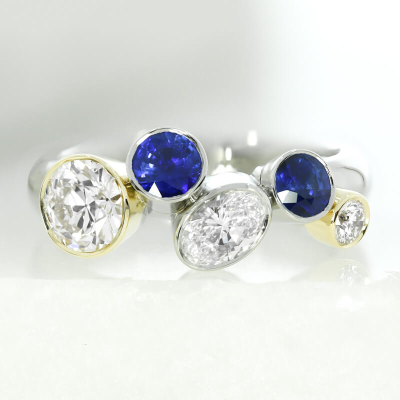 A bespoke engagement ring commission, featuring oval and round diamonds and blue sapphires